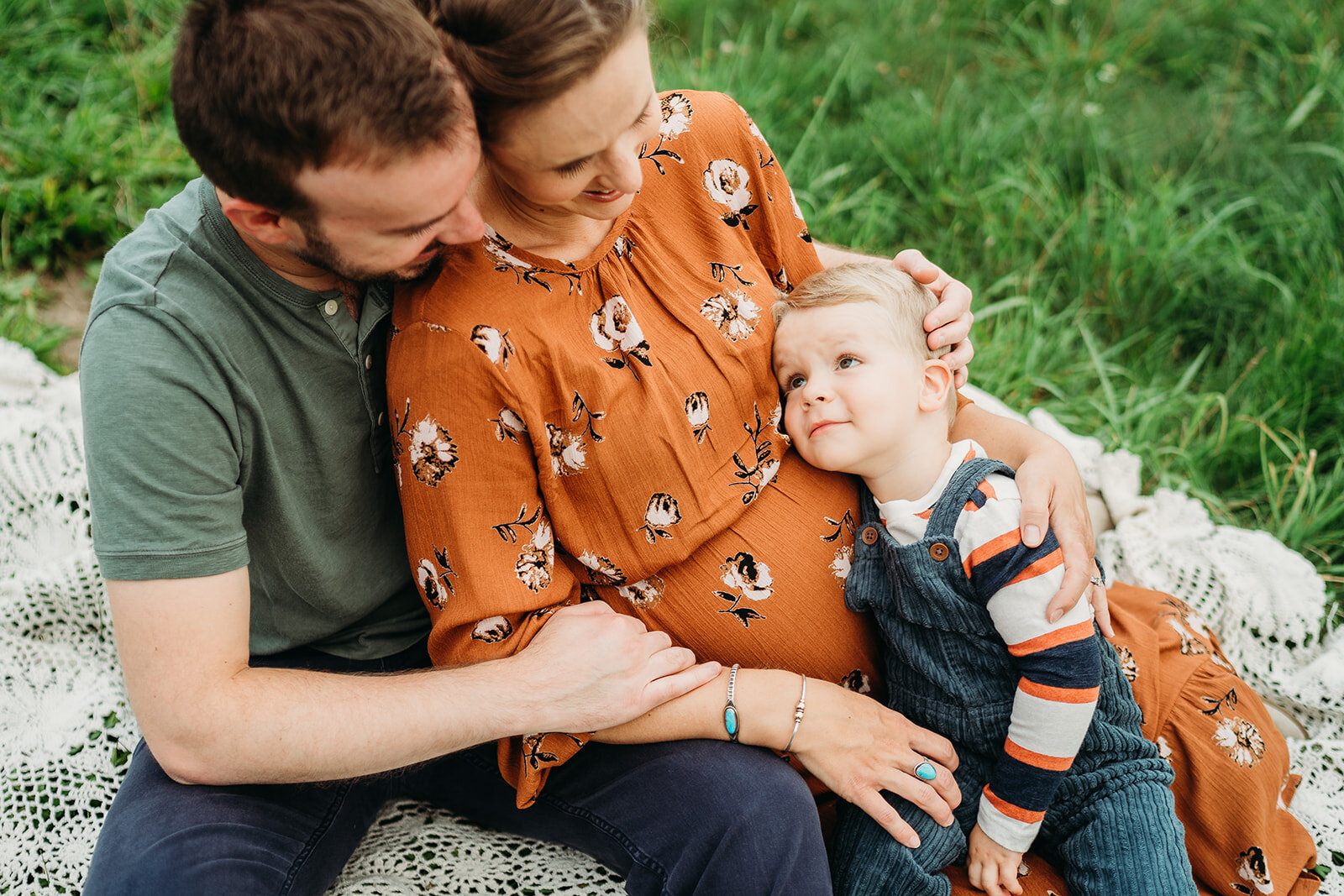 toddler big brother snuggles pregnant moms belly during family photos