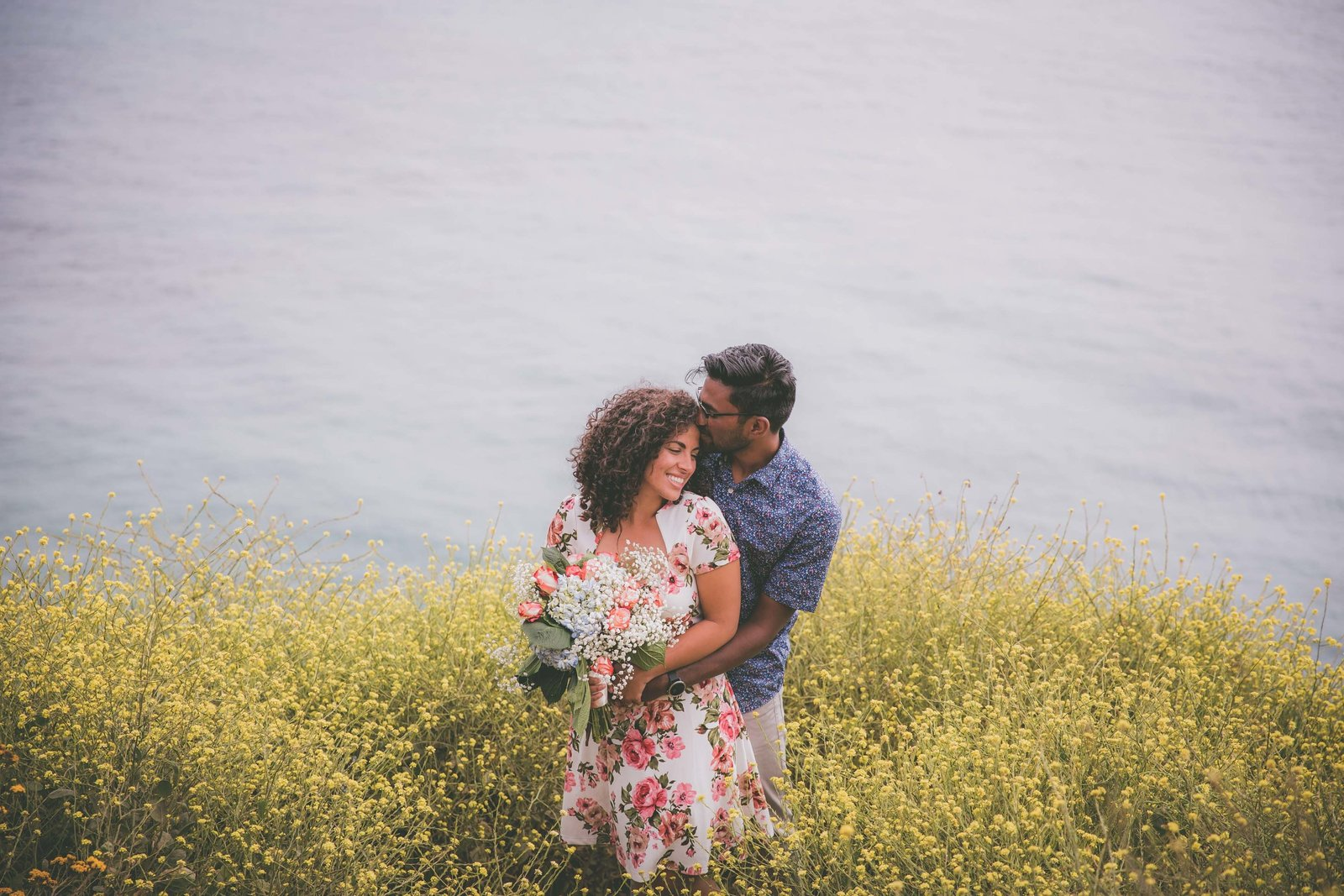 Man kisses future wife in field on yellow wildflowers in Big Sur.