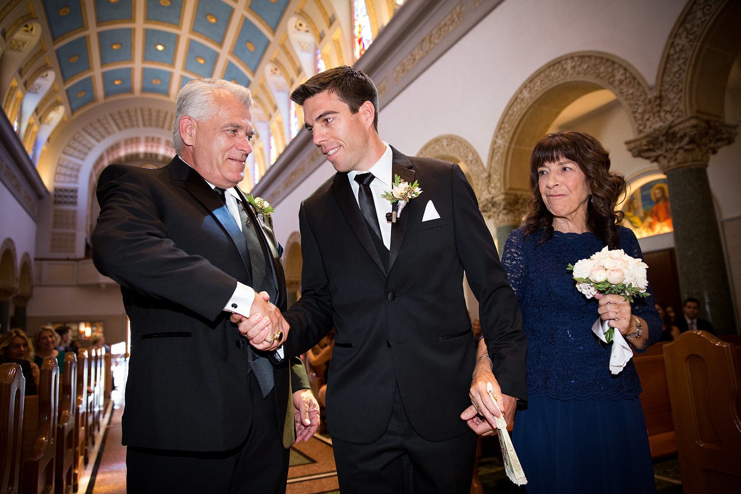 groom with his parents at ceremony