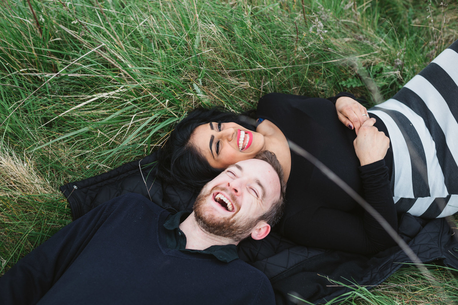 Natural photograph of relaxed couple laughing and cuddling outside laying in the grass in the Norfolk countryside