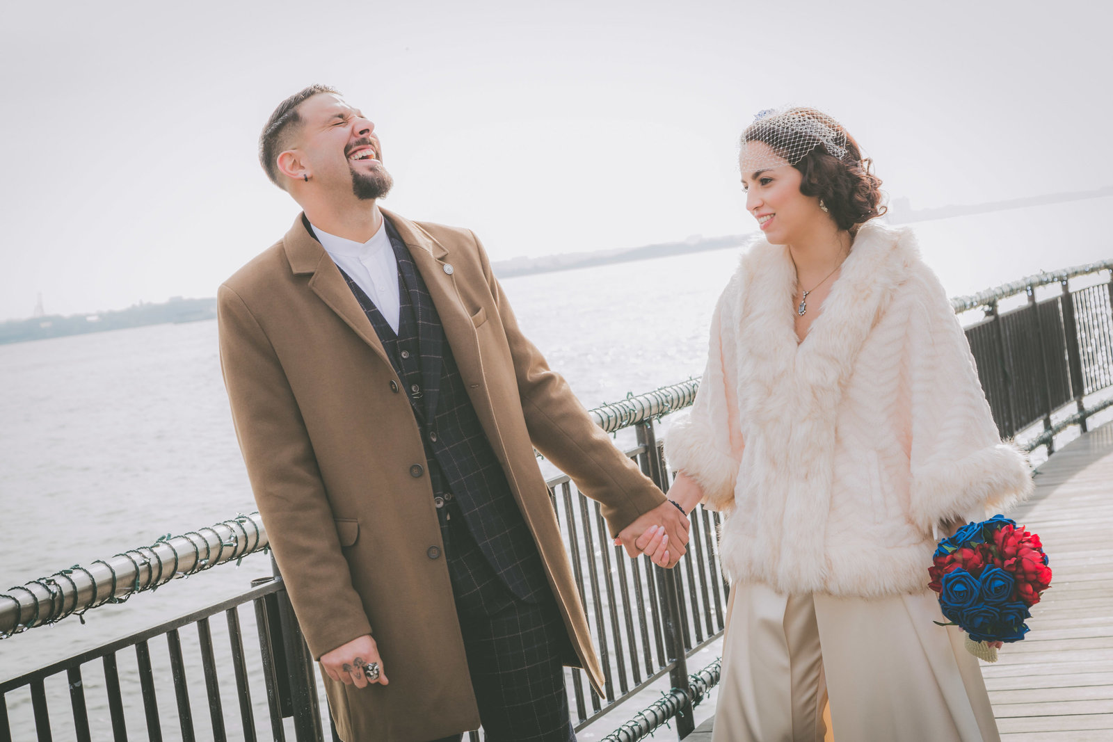 A groom laughs while wife looks on during Jersey City wedding.