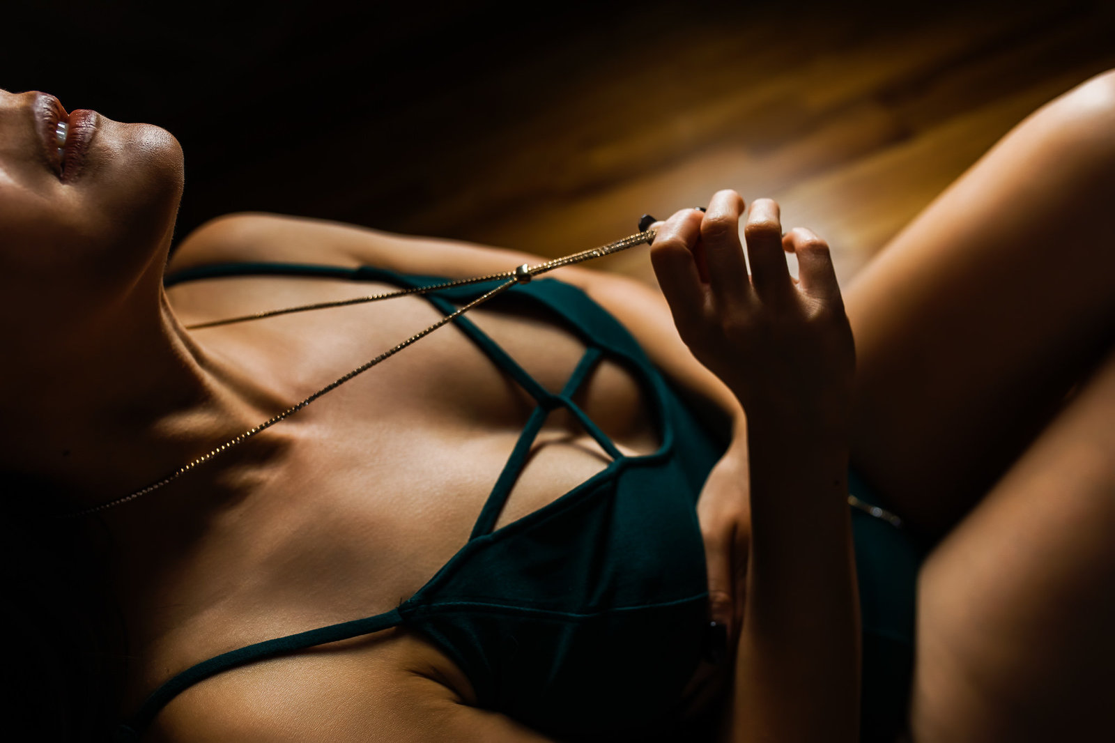 Dark and moody boudoir photo of a woman playing with her necklace