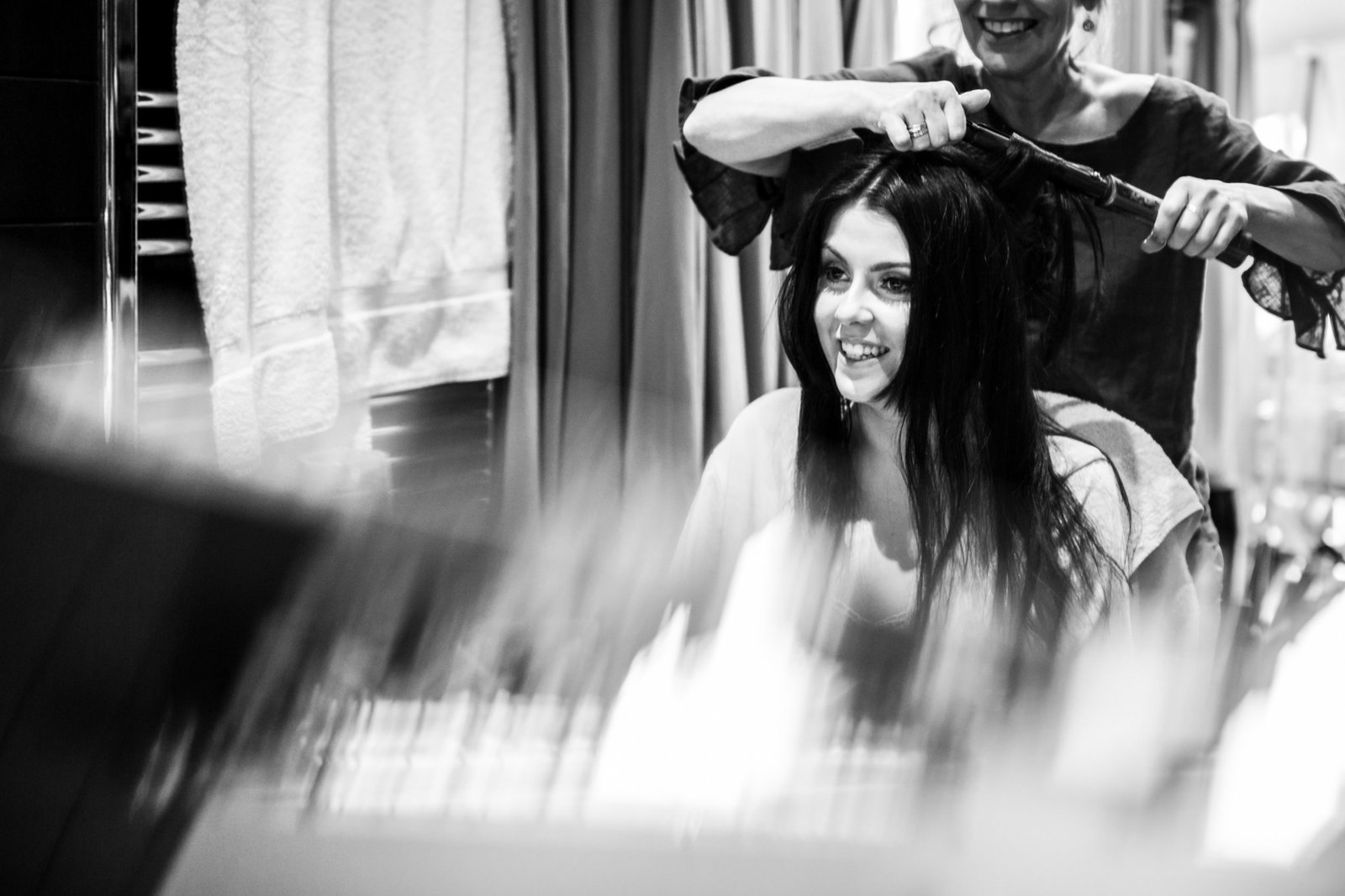 The Bride smiles and looks into a mirror whilst she has her hair done in preparation for her wedding day in Norfolk.