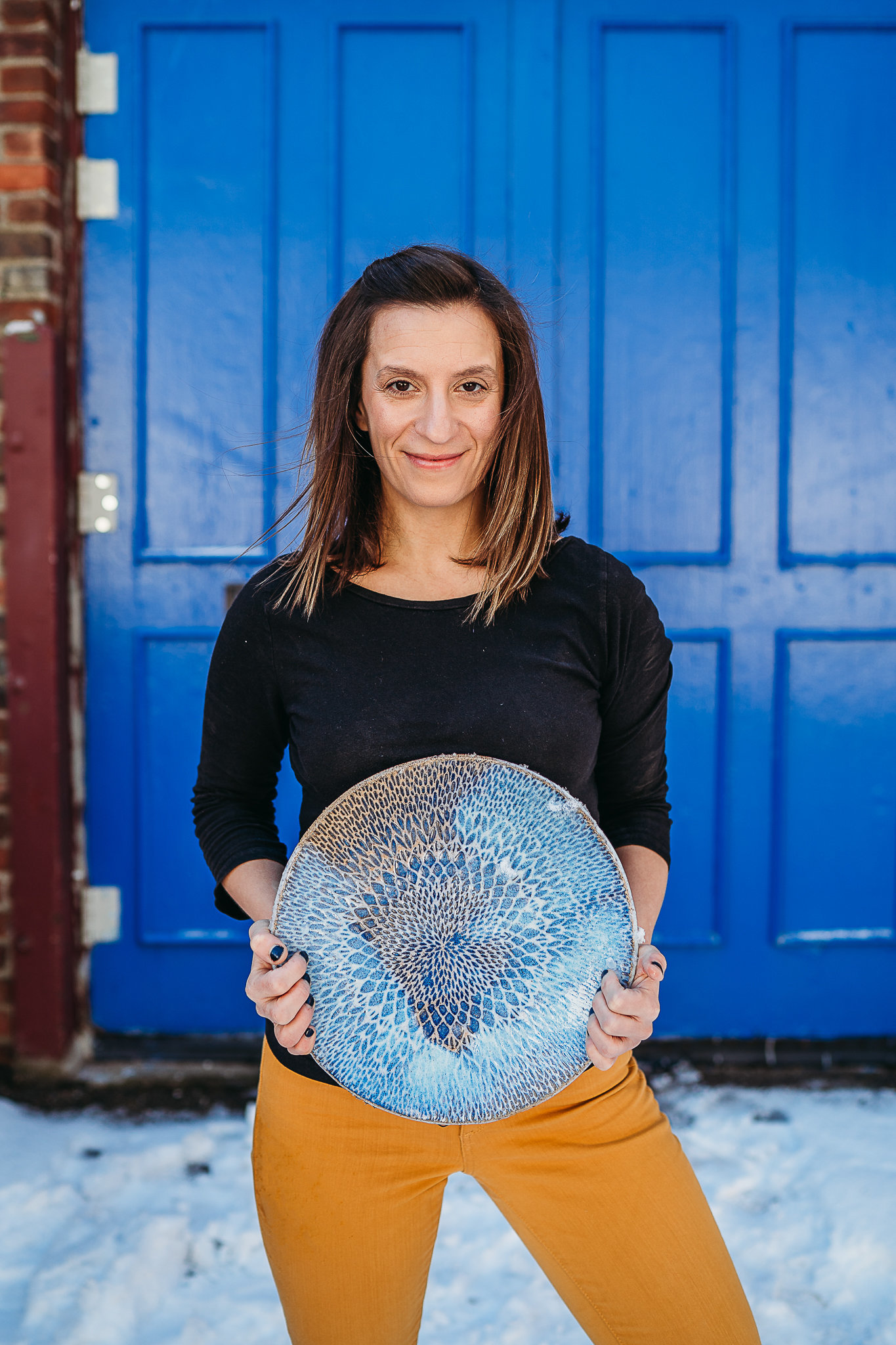 female potter holds platter in front of bright blue door