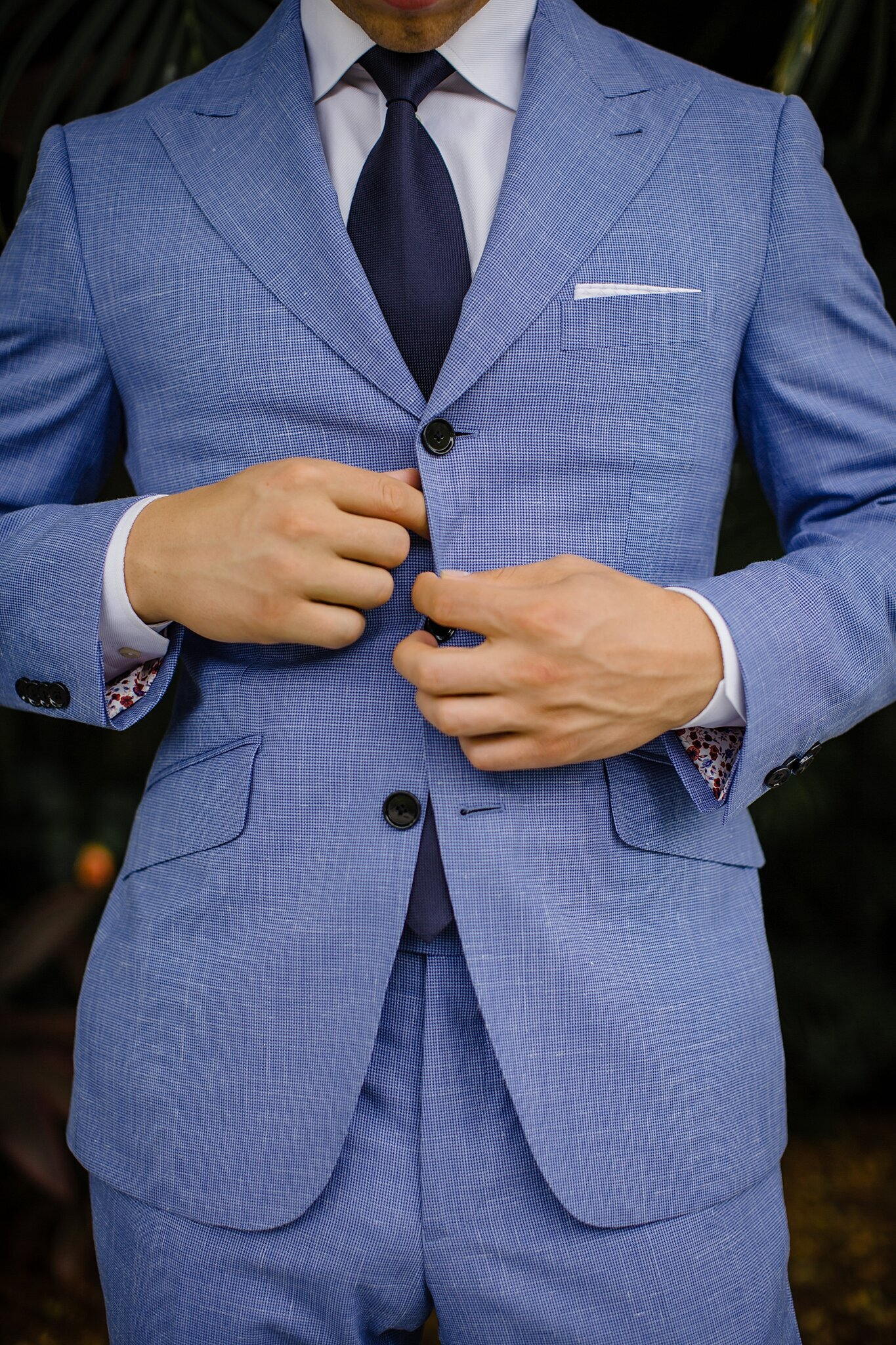 groom buttoning blue suit