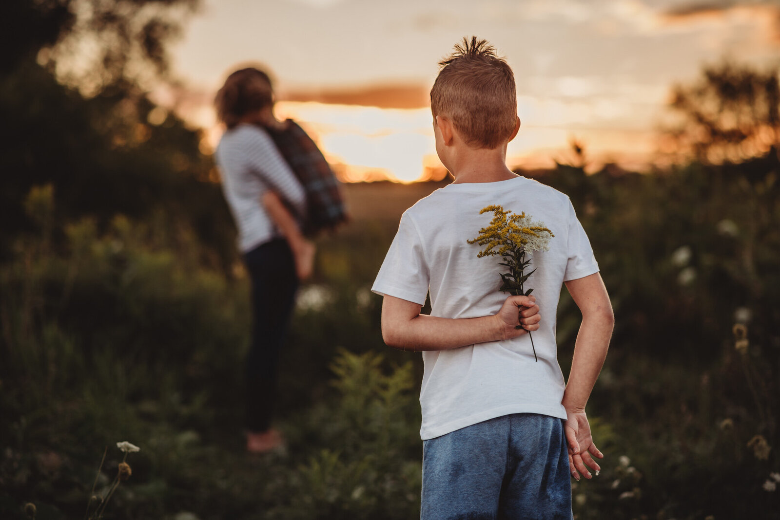 Son holding flowers behind his back for his mother at sunset