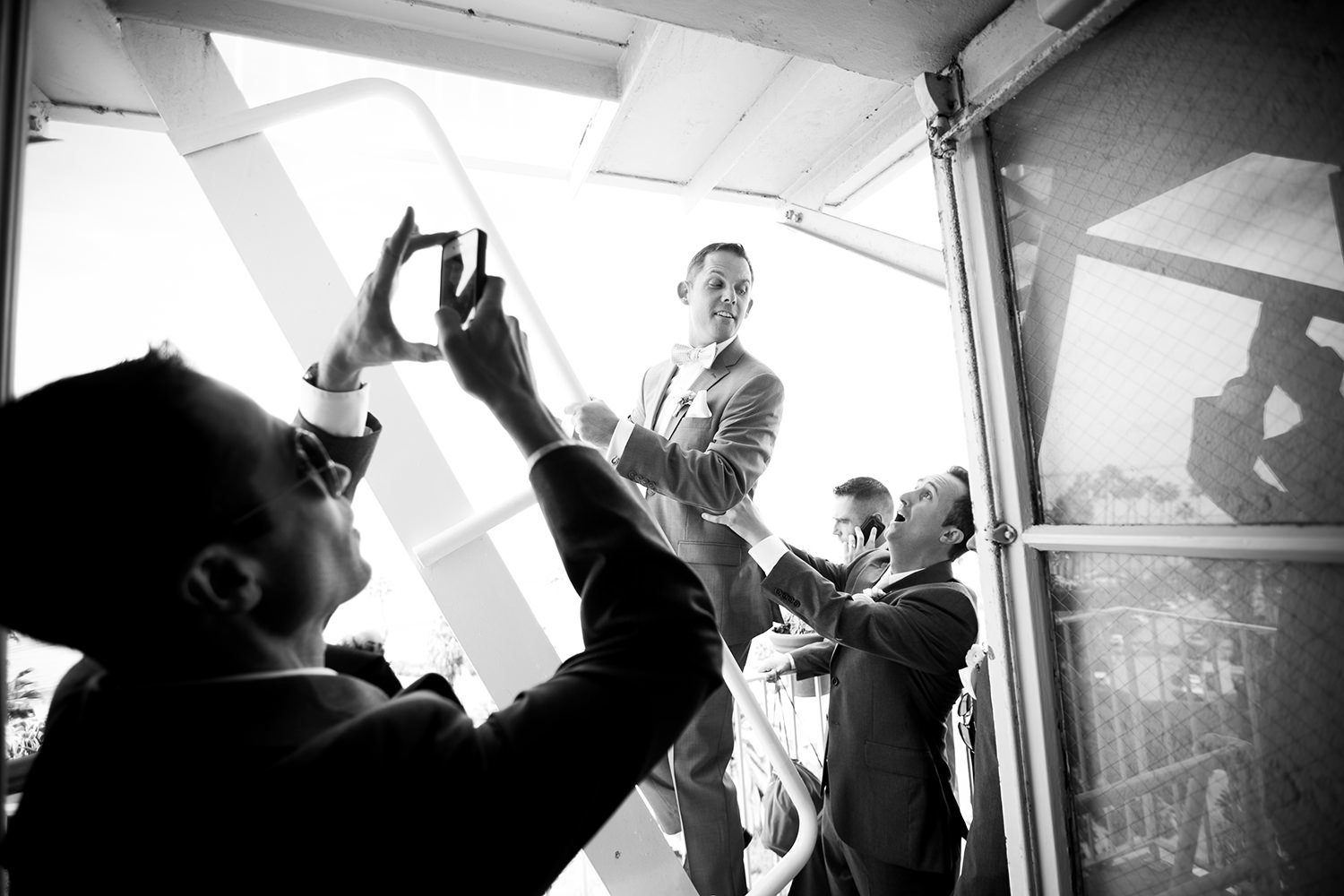 Photojournalistic moment captured of the groom and his groomsmen on the fire escape
