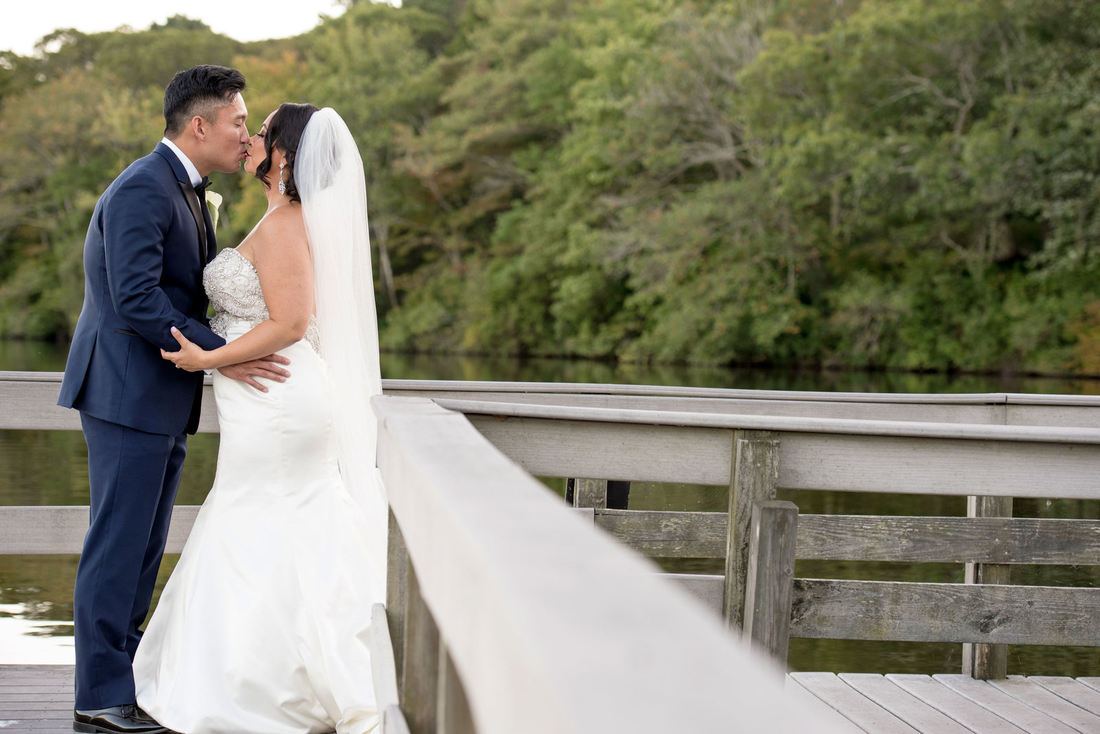Bride and groom kissing on dock at Camp Pa-Qua-Tuck