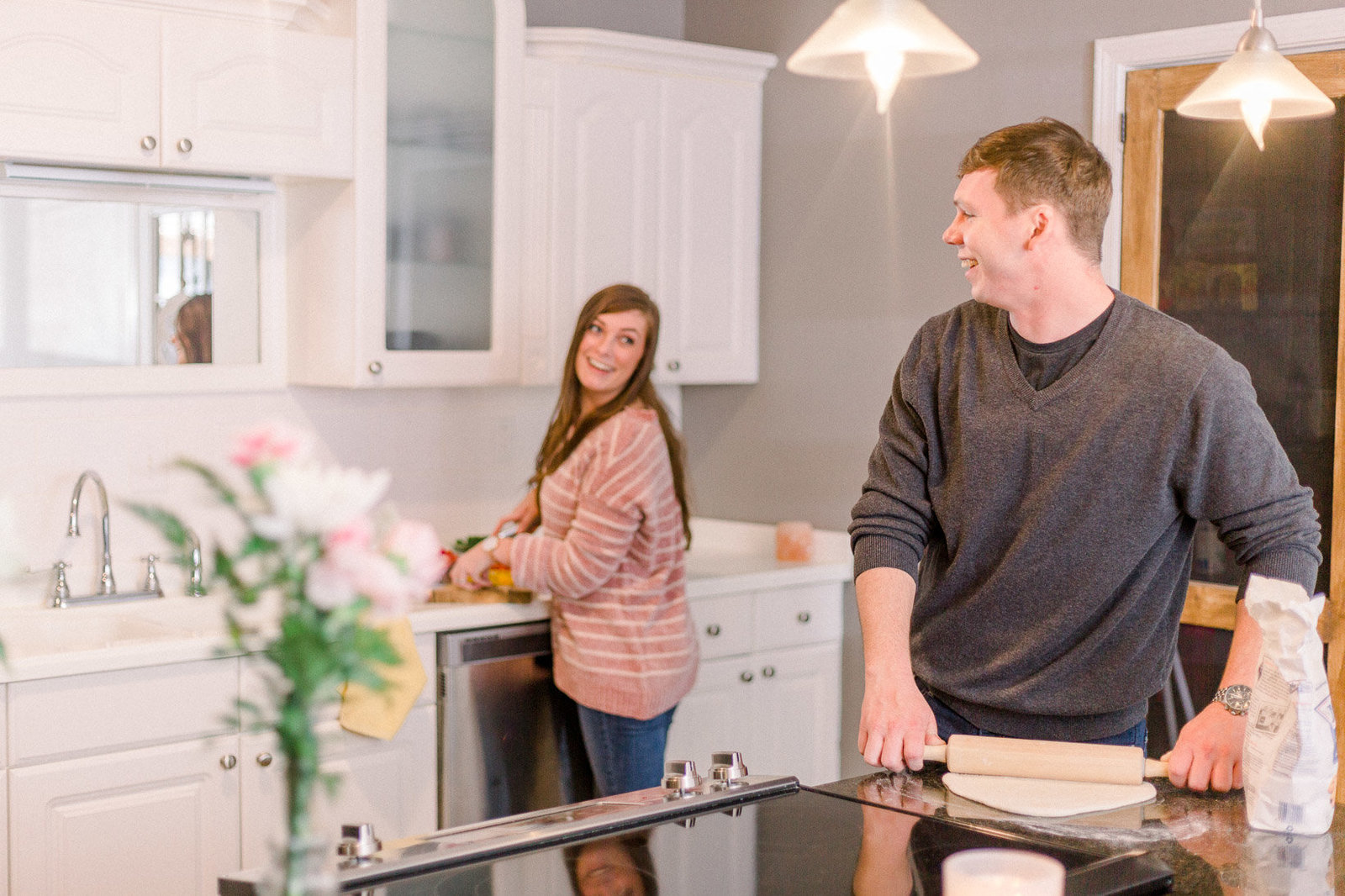 Couple laughing together as they cook dinner captured by Staci Addison Photography