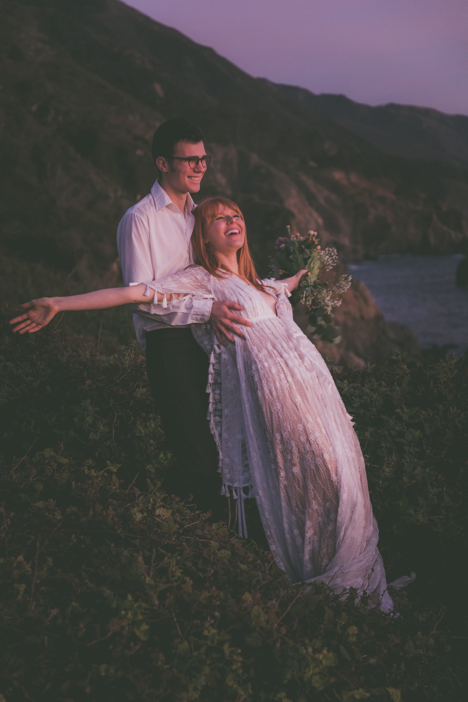 A couple does a trust fall while enjoying the sunset in Big Sur.