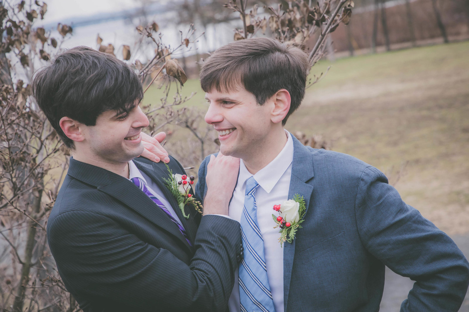 Grooms look at each other and smile in park.
