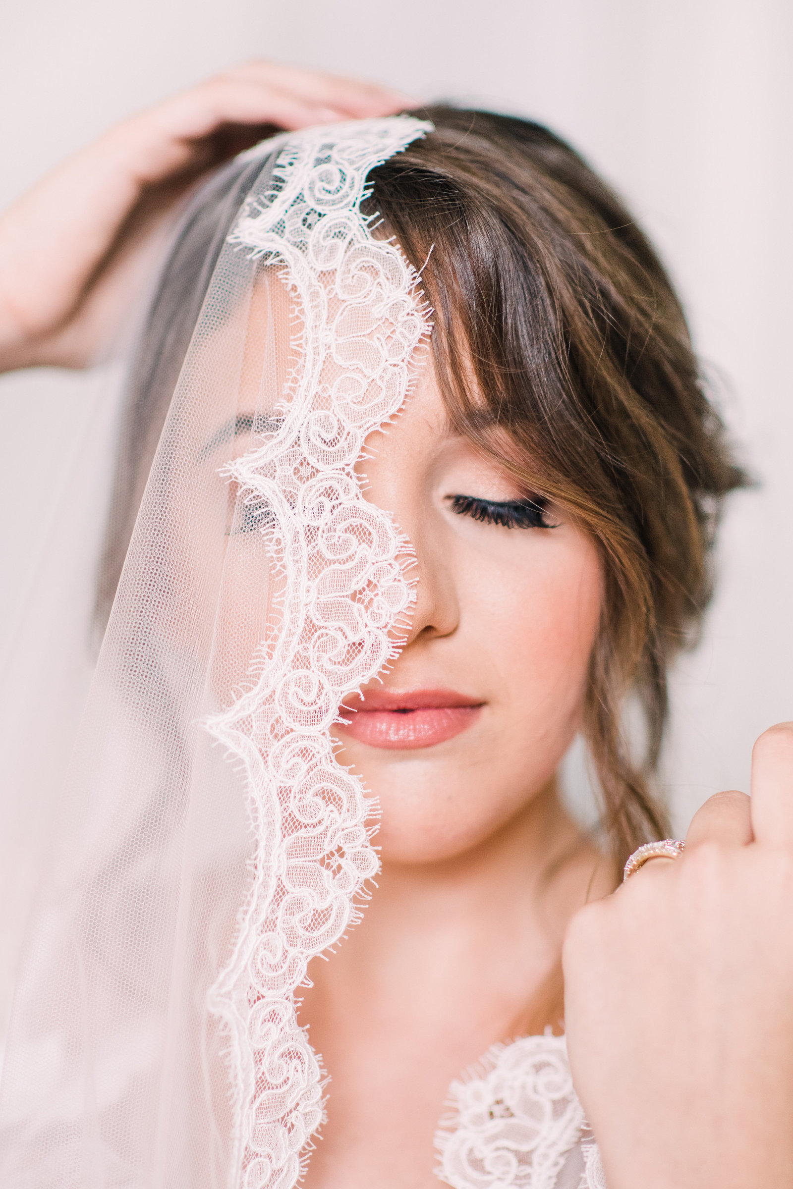 fine art portrait of bride with lace veil over her face and eyes closed