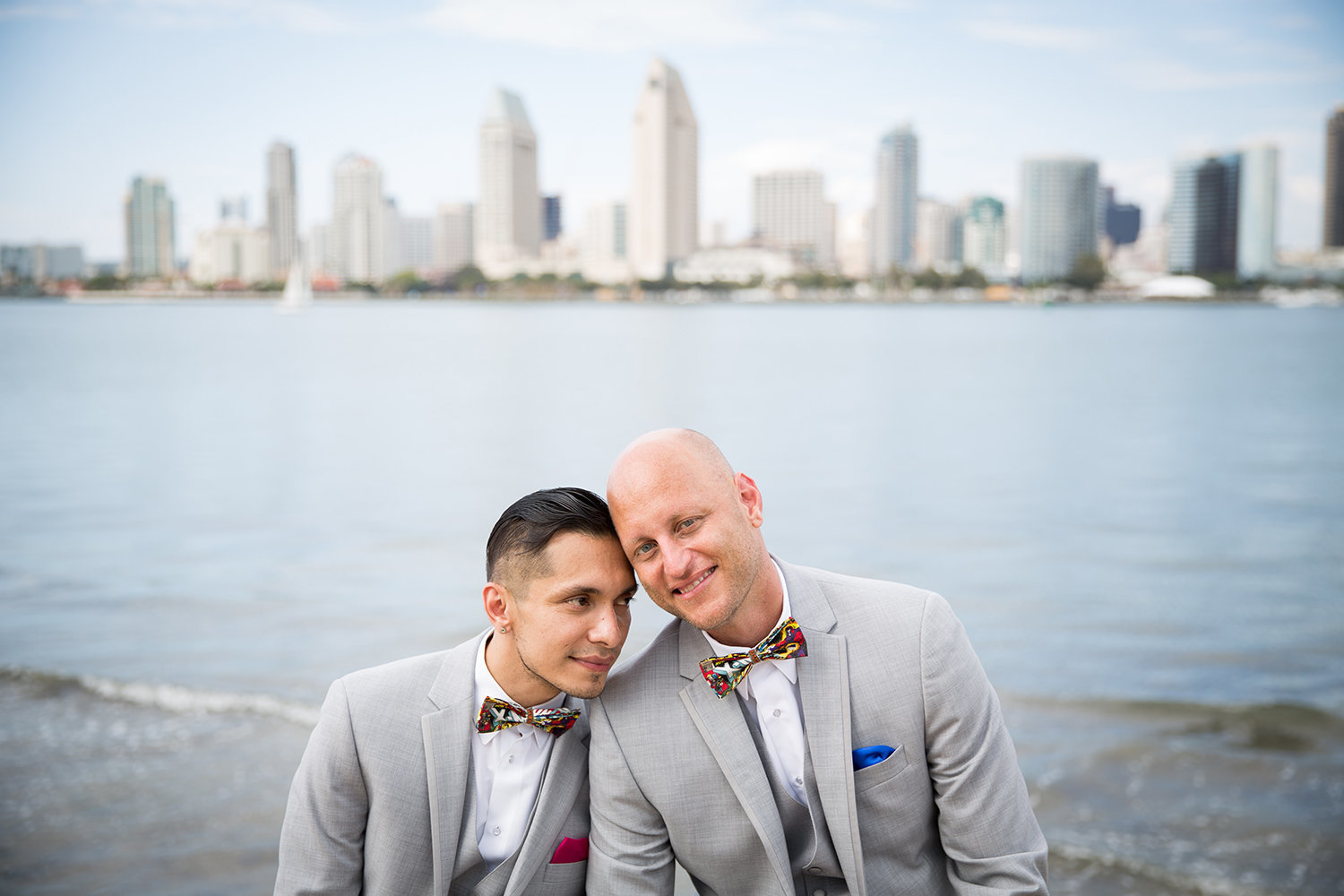 Portrait of a sweet gay couple with the San Diego skyline as the backdrop\