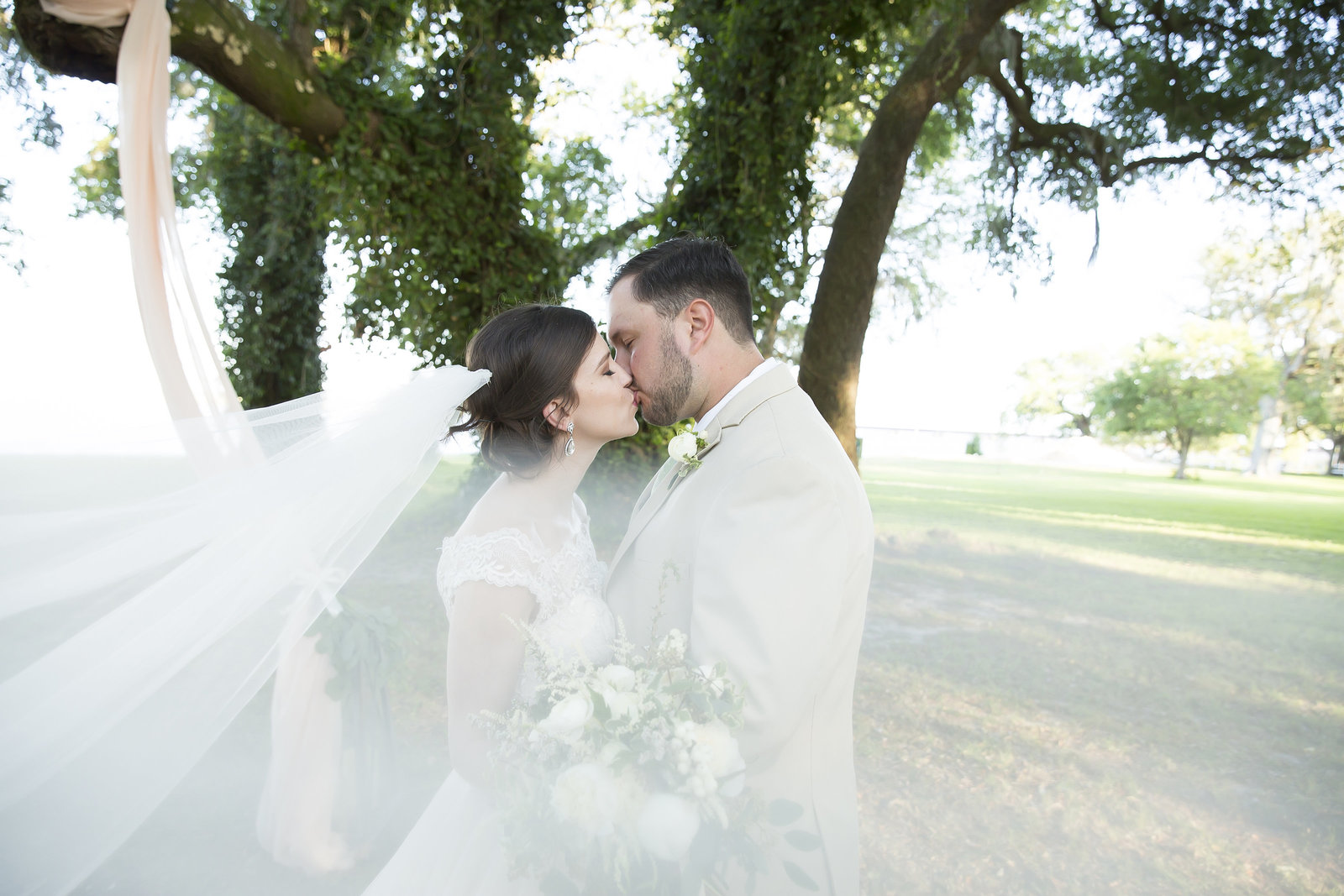 Bride and Groom share a kiss on their wedding day at the Old Place in Gautier