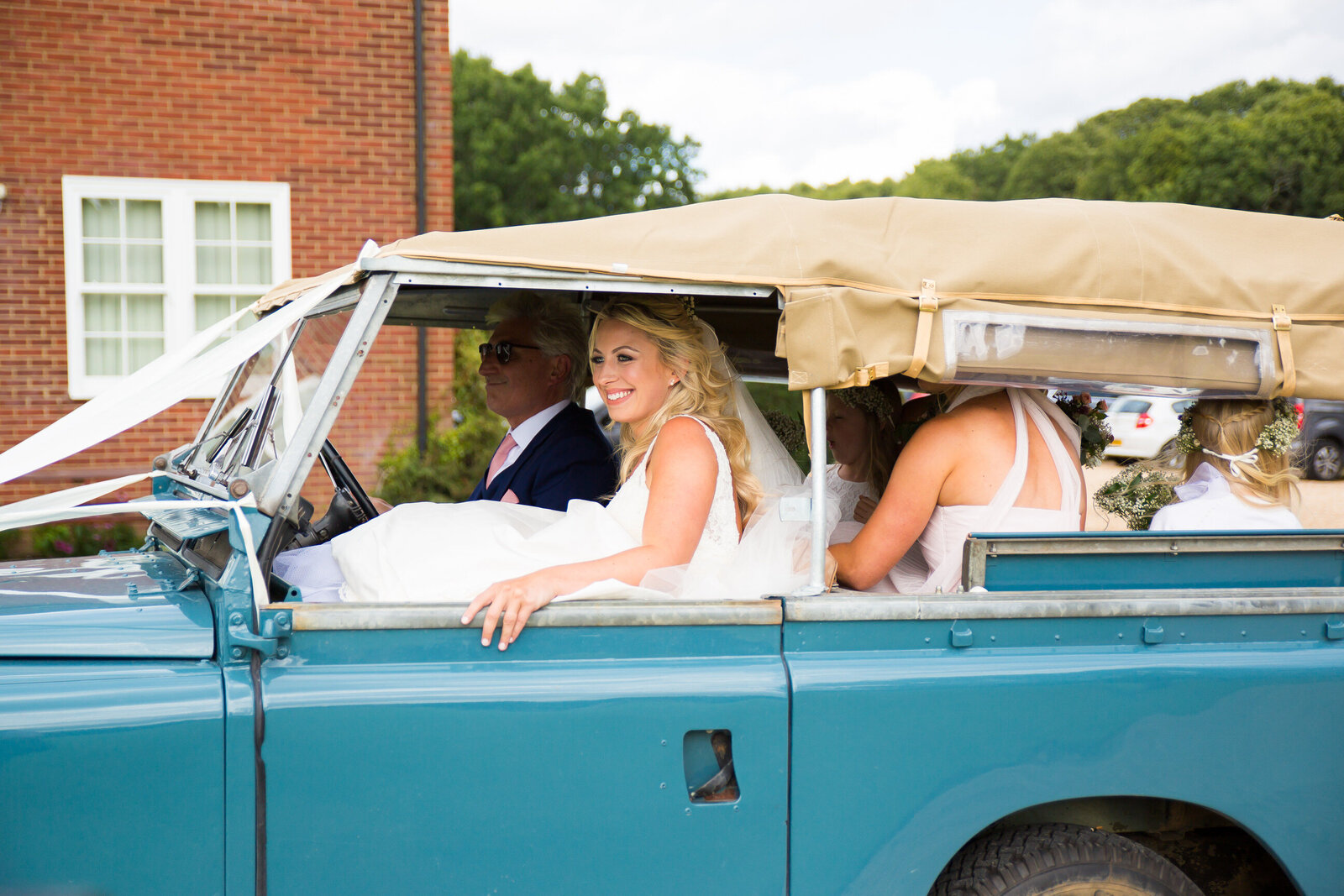Wedding photography of a bride in a car on her way to get married at Highfield School Capel in Surrey. Photography by Lynsey Grace Photography.