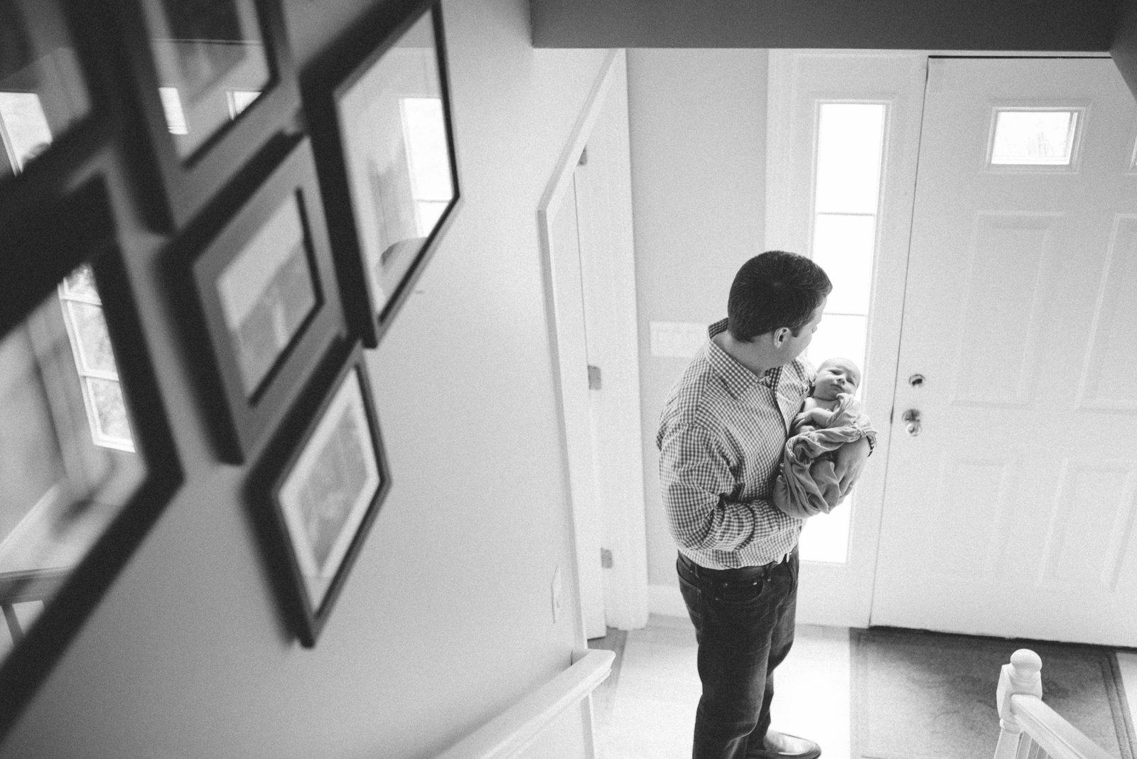 Newnborn at home in father's hands in Boston lifestyle home session