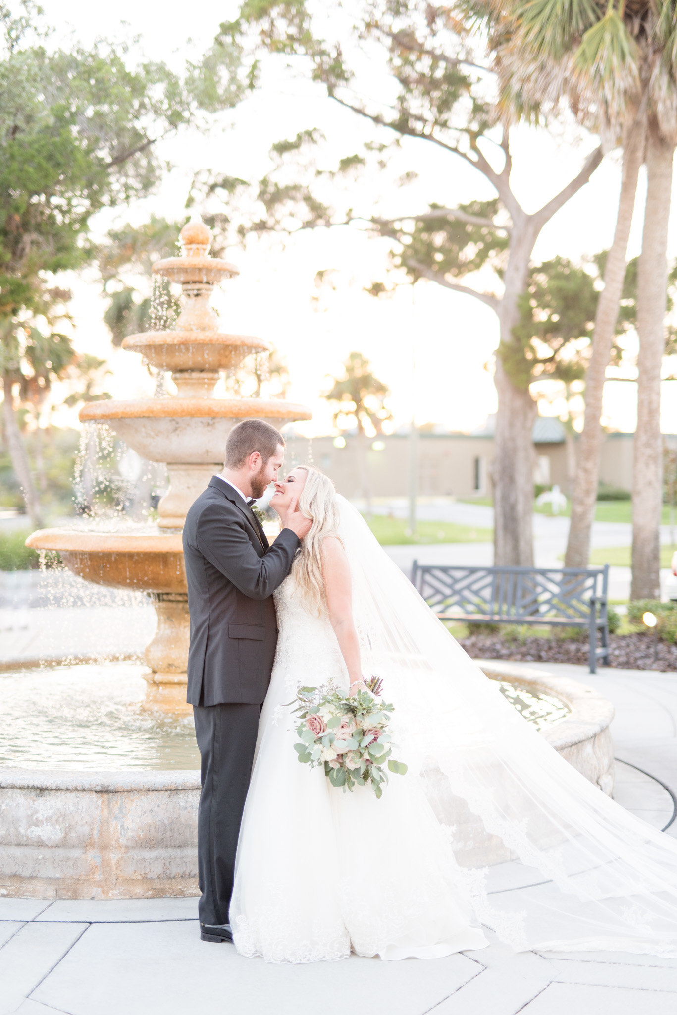 Bride and Groom kiss in front of fountain.