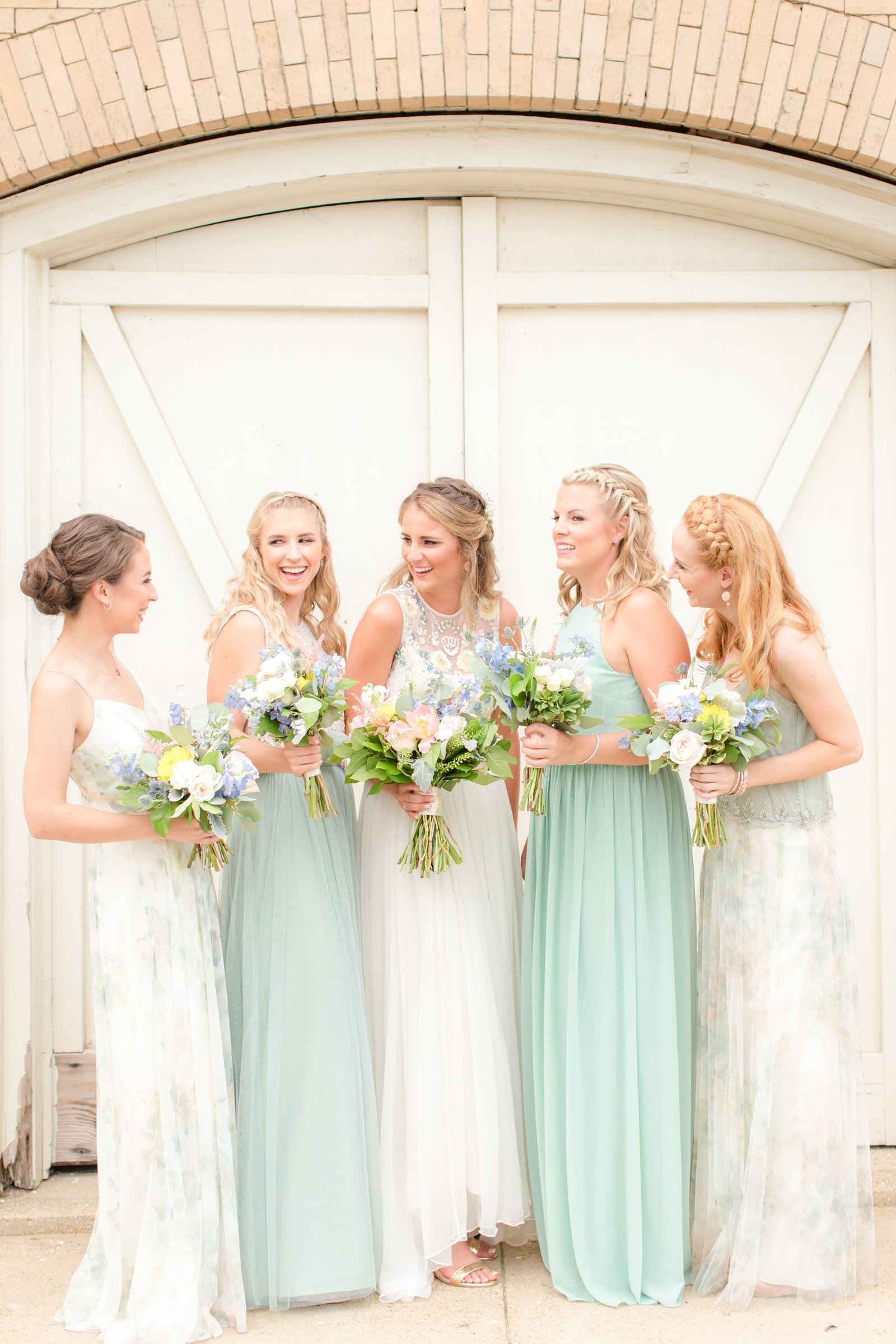 Bridesmaids wearing soft green and lush florals