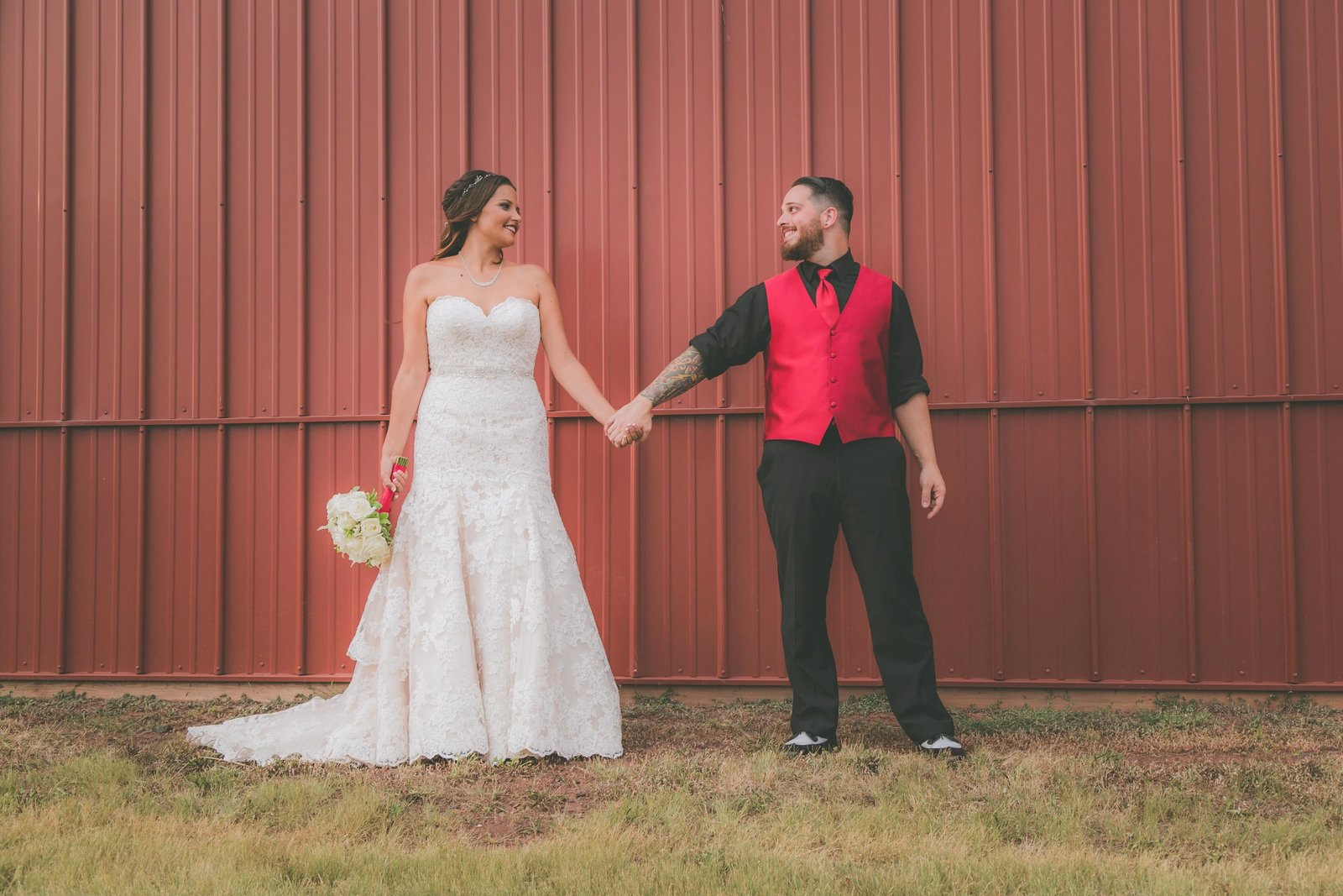 Bride and groom hold hands and look at one another against red barn background.
