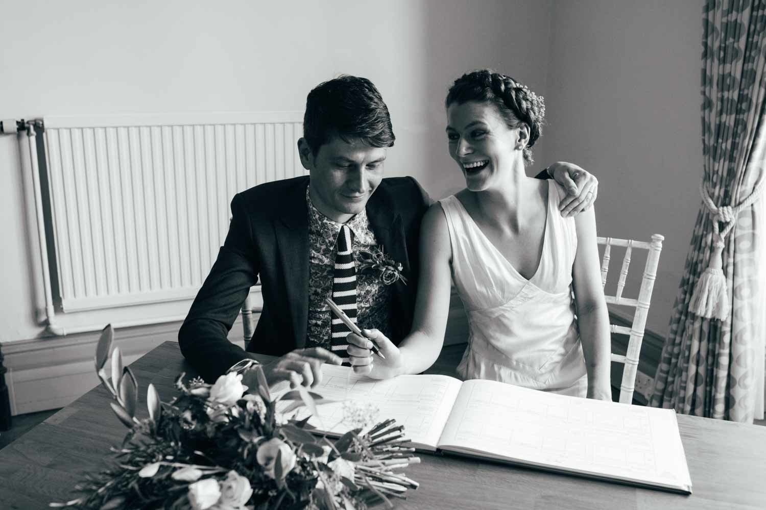 Natural black and white photograph of relaxed bride and groom signing the wedding ceremony register in Norwich Castle