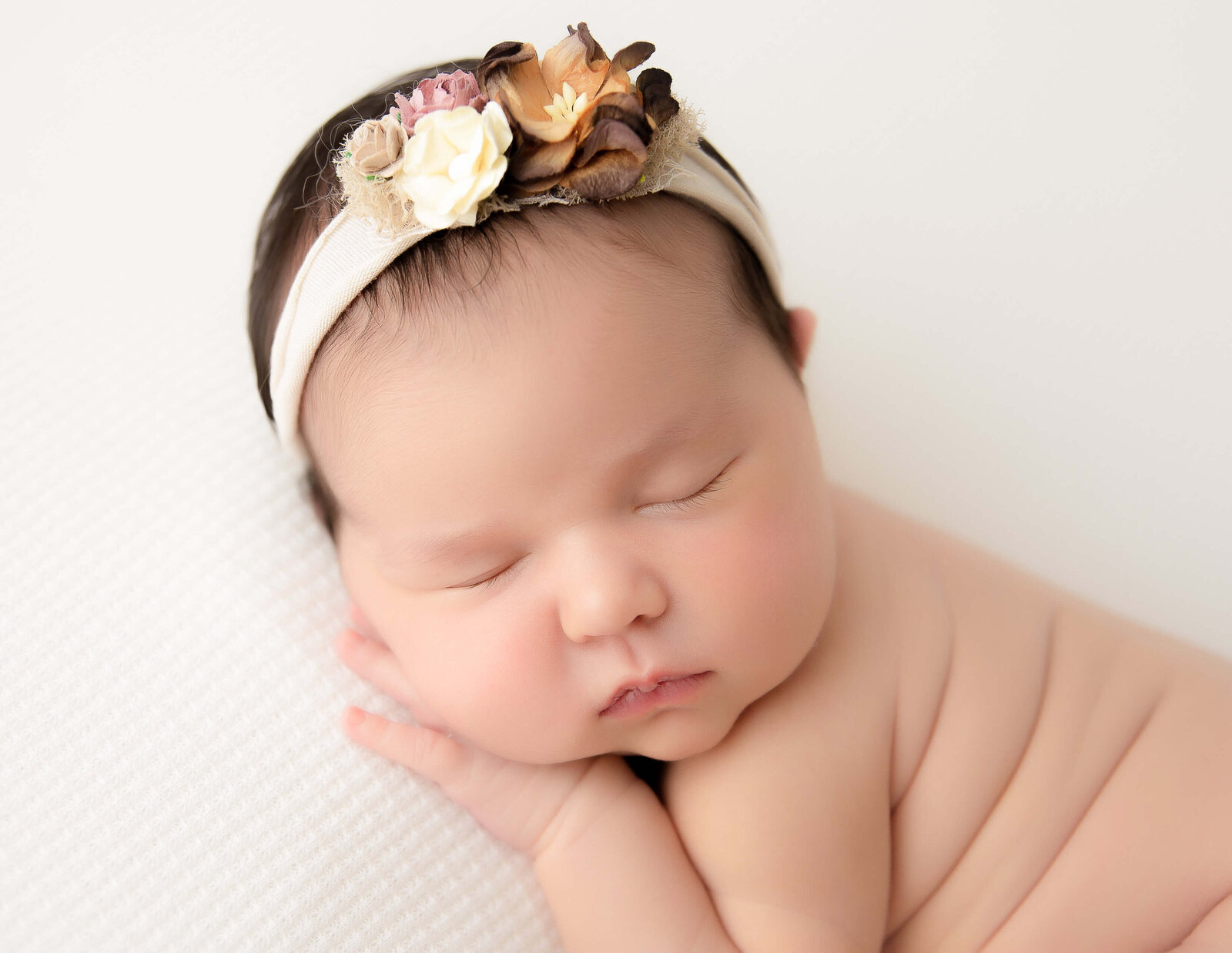 Newborn girl posed in our Rochester, NY studio.