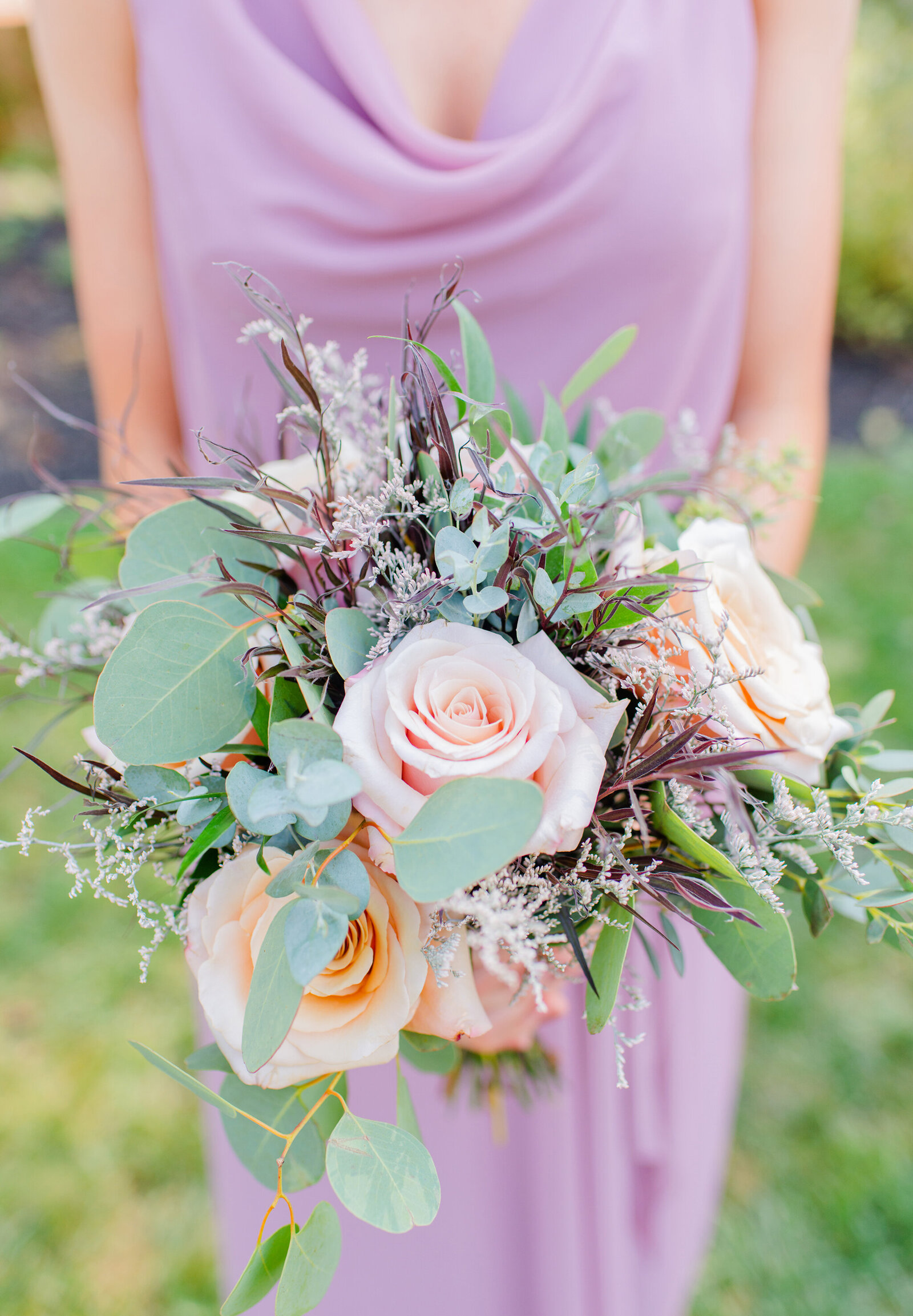bridesmaid in purple gown holding bridal bouquet
