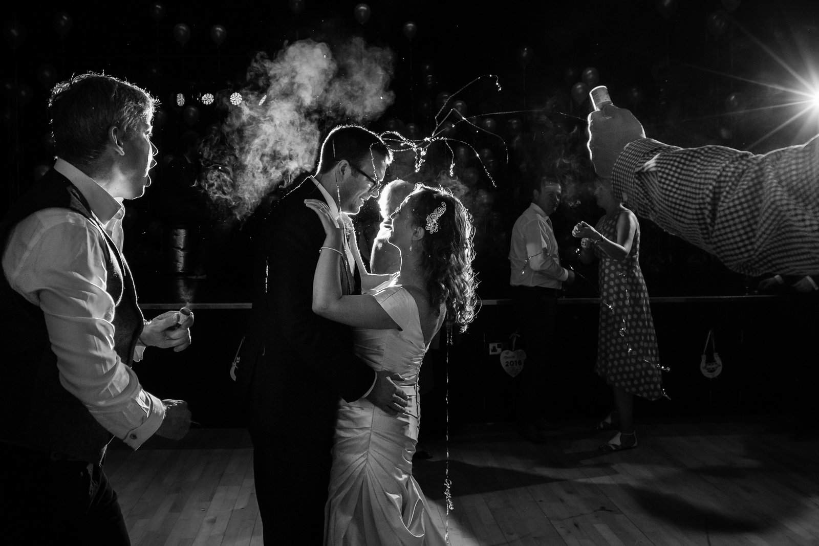 Bride and Groom stand on the dance floor at a Norfolk venue, look at each other and smile whilst wedding guests fire party poppers at them.
