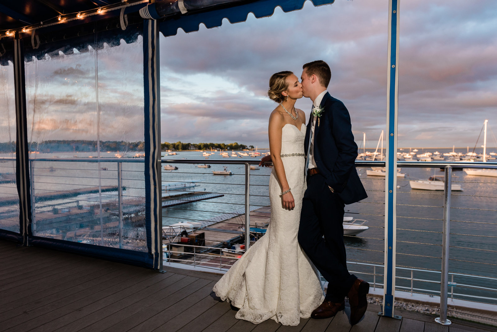 A couple shares a kiss on the deck at their Duxbury Bay Maritime School wedding at sunset
