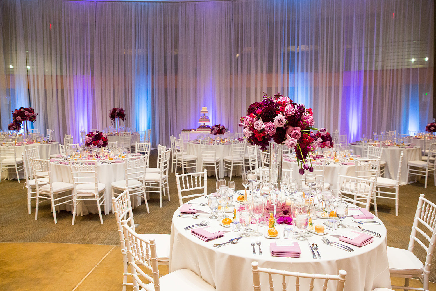 reception tables with pink and purple uplighting