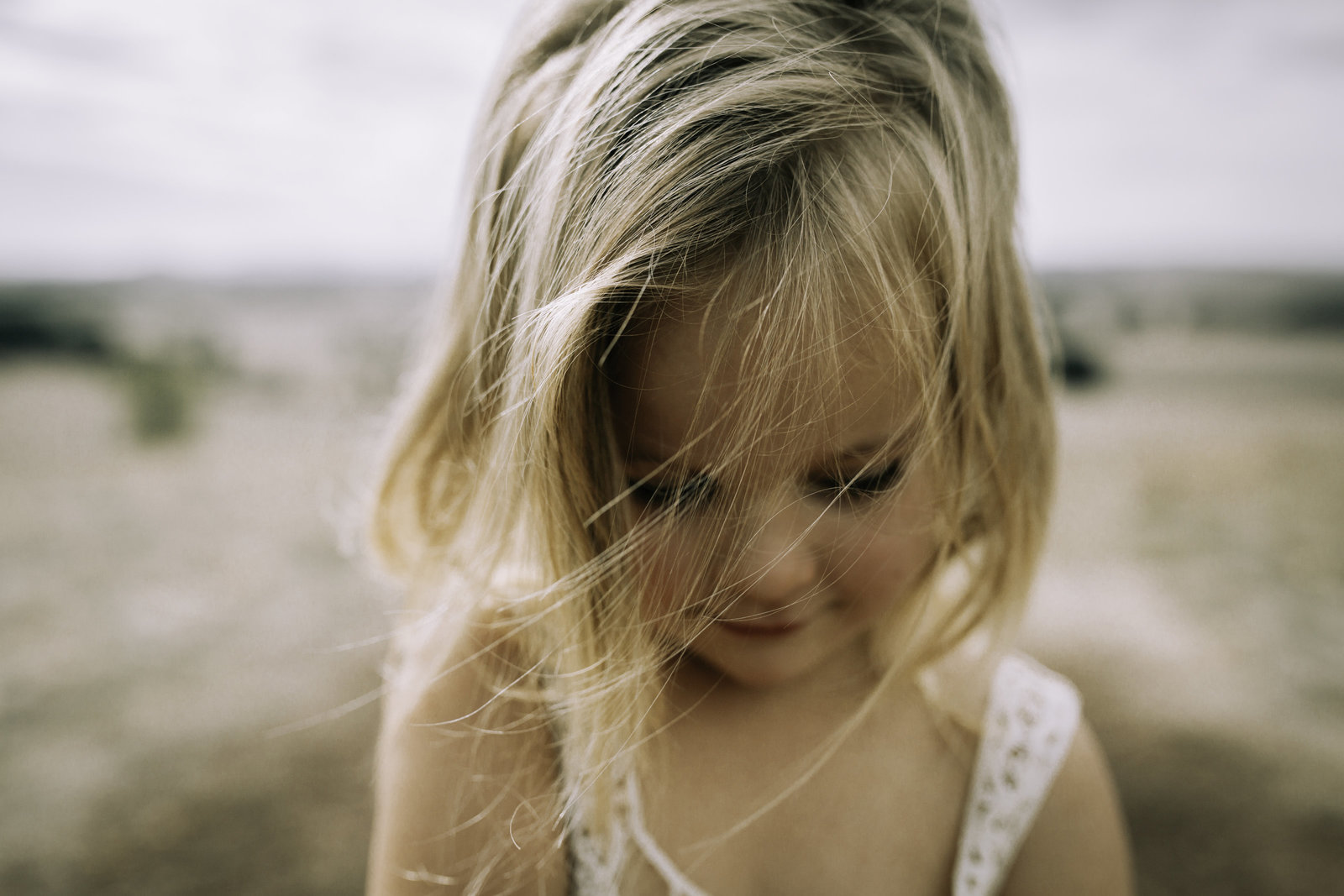 Little girl with blonde hair looking down with long lashes. Wind in hair in open field. Melbourne Family Photographer Sapphire and Stone Photography