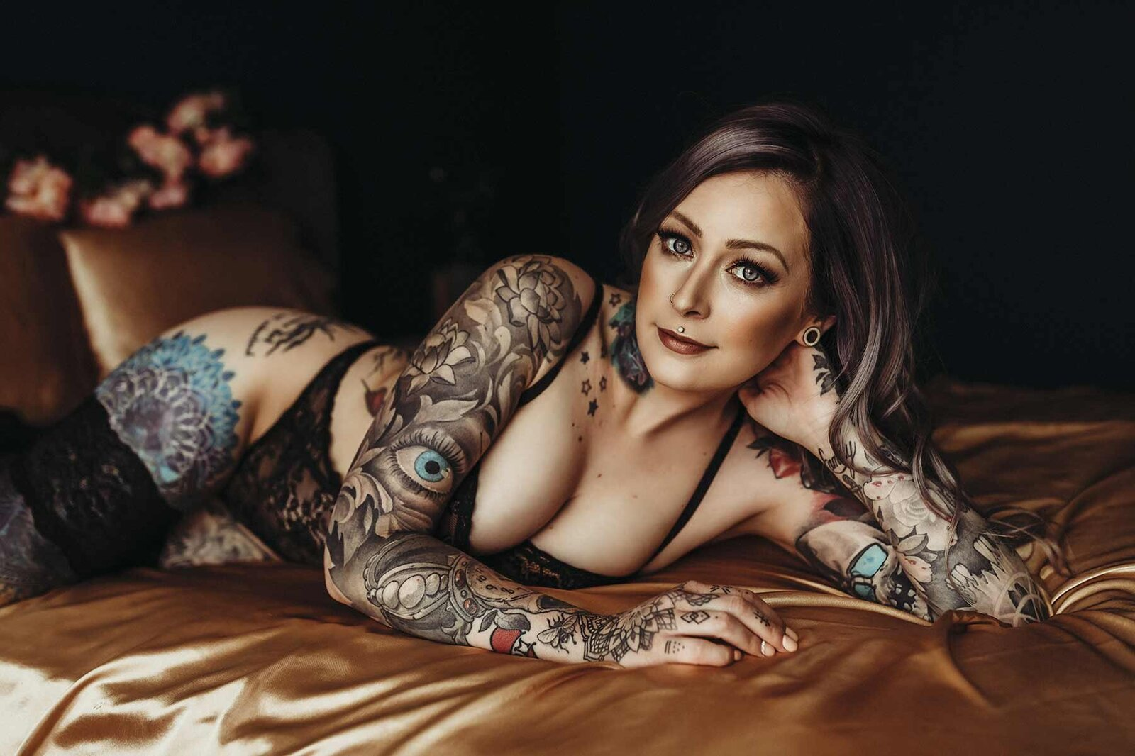 Woman with tattoos laying on copper silk sheets
