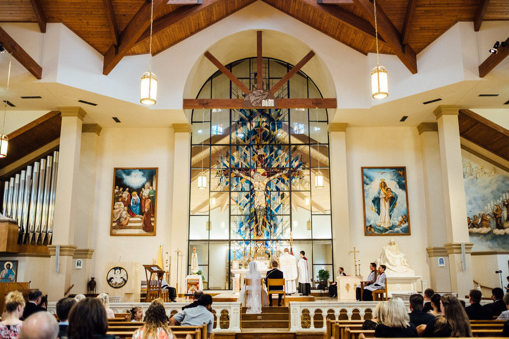 Wide angle of bride and groom sitting at the altar at their Traditional Latin Nuptial Mass