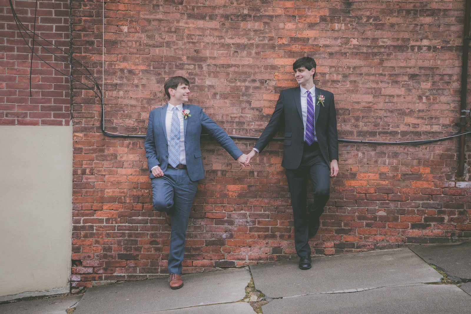 Two grooms hold hands against a brick wall while smiling.