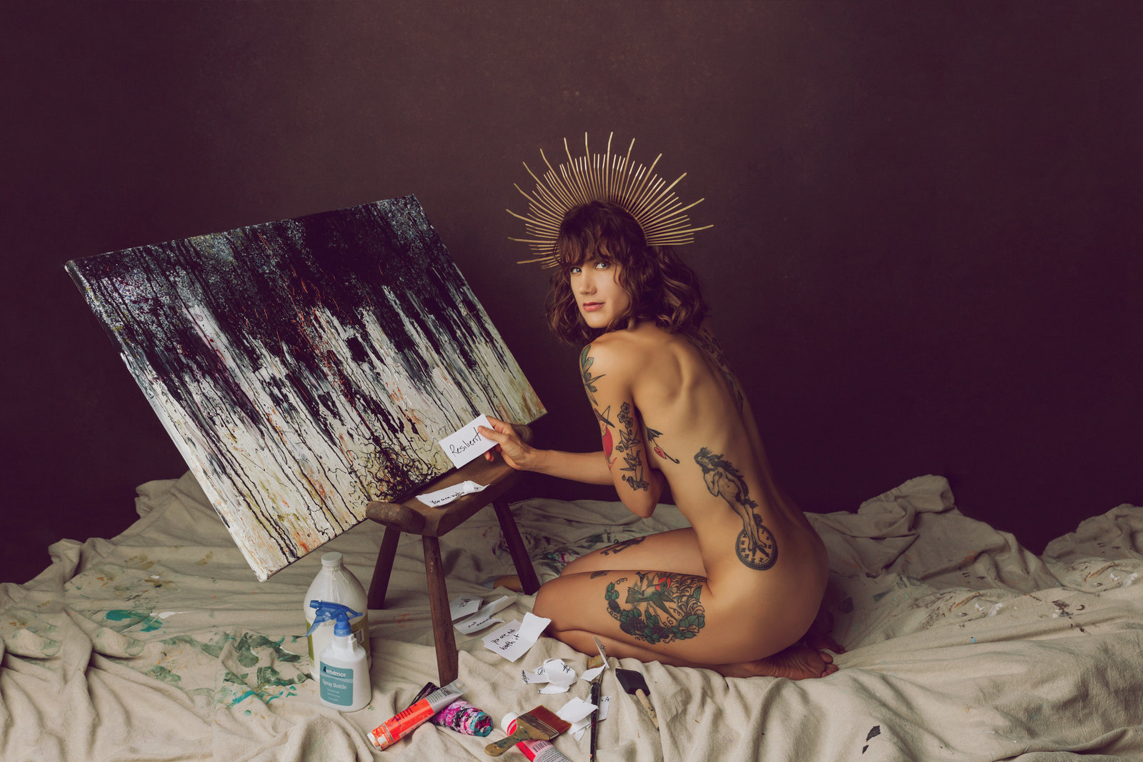 Nude fine art portrait of a woman kneeling on the ground painting, looking over her shoulder at the camera.