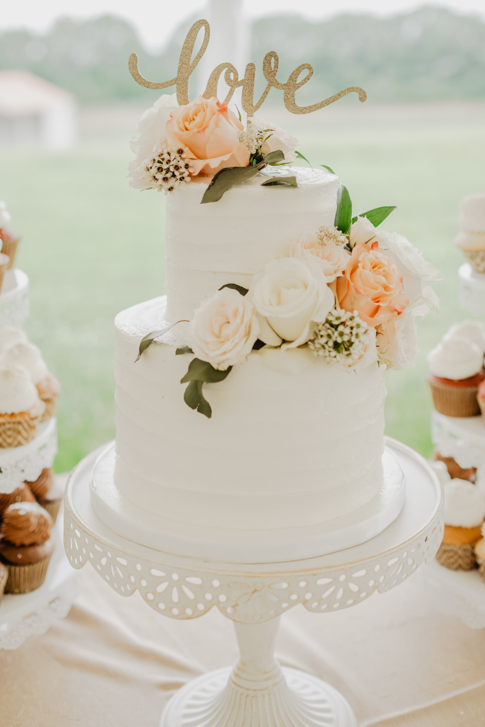 Classic white buttercream wedding cake with white and peach rose accents at Rippavilla Plantation.