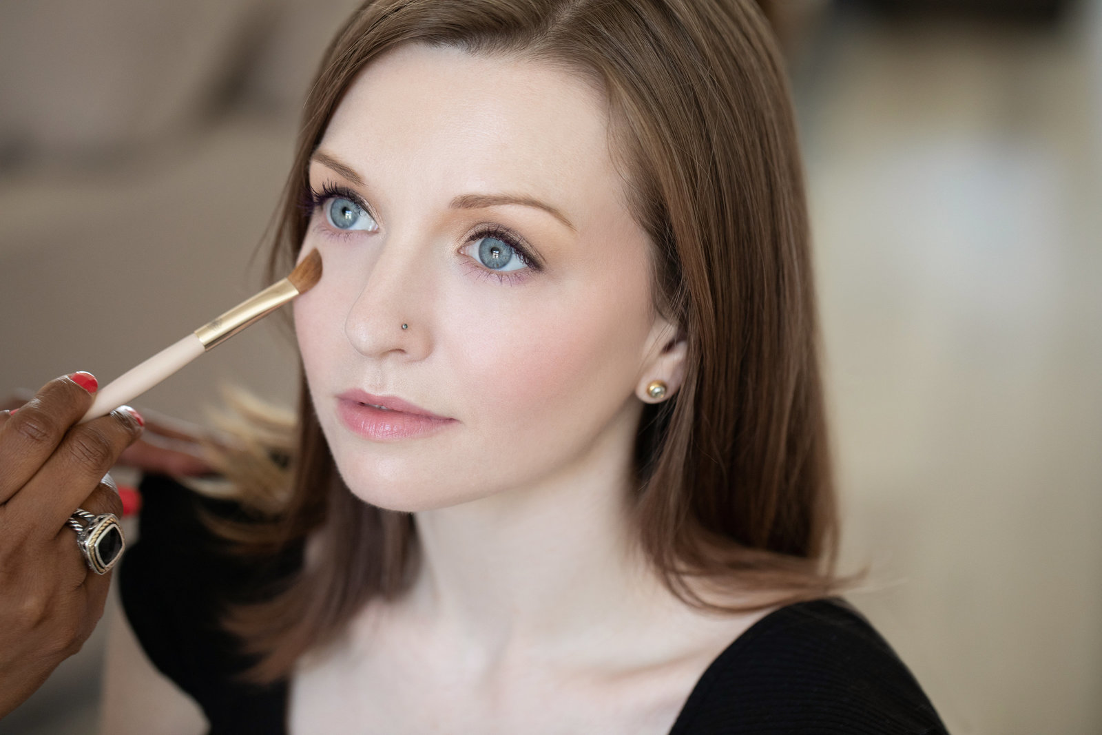 Makeup artist applying make up to young women's undereye