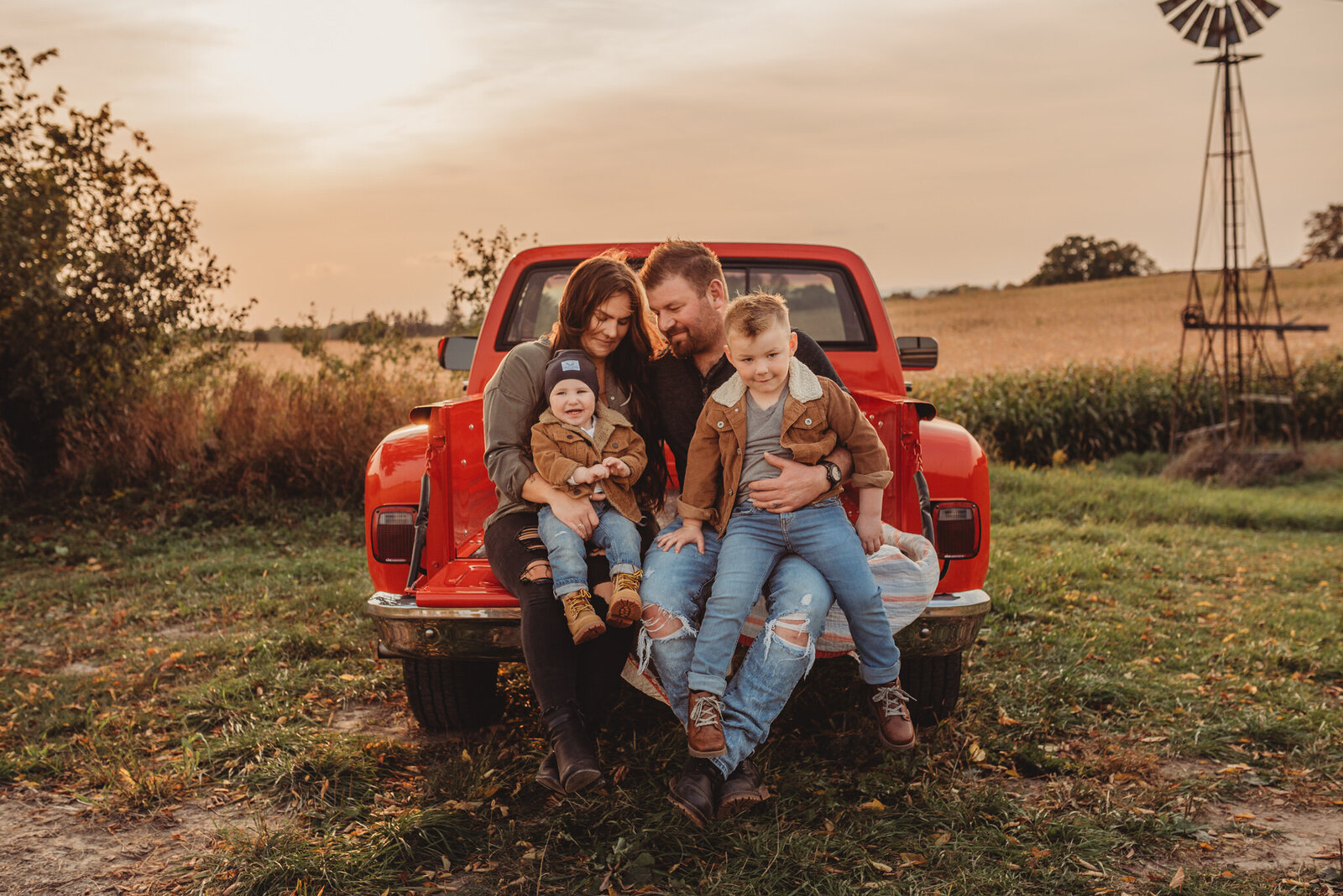 Family of four in the back of a red pick-up truck at sunset in Oshawa