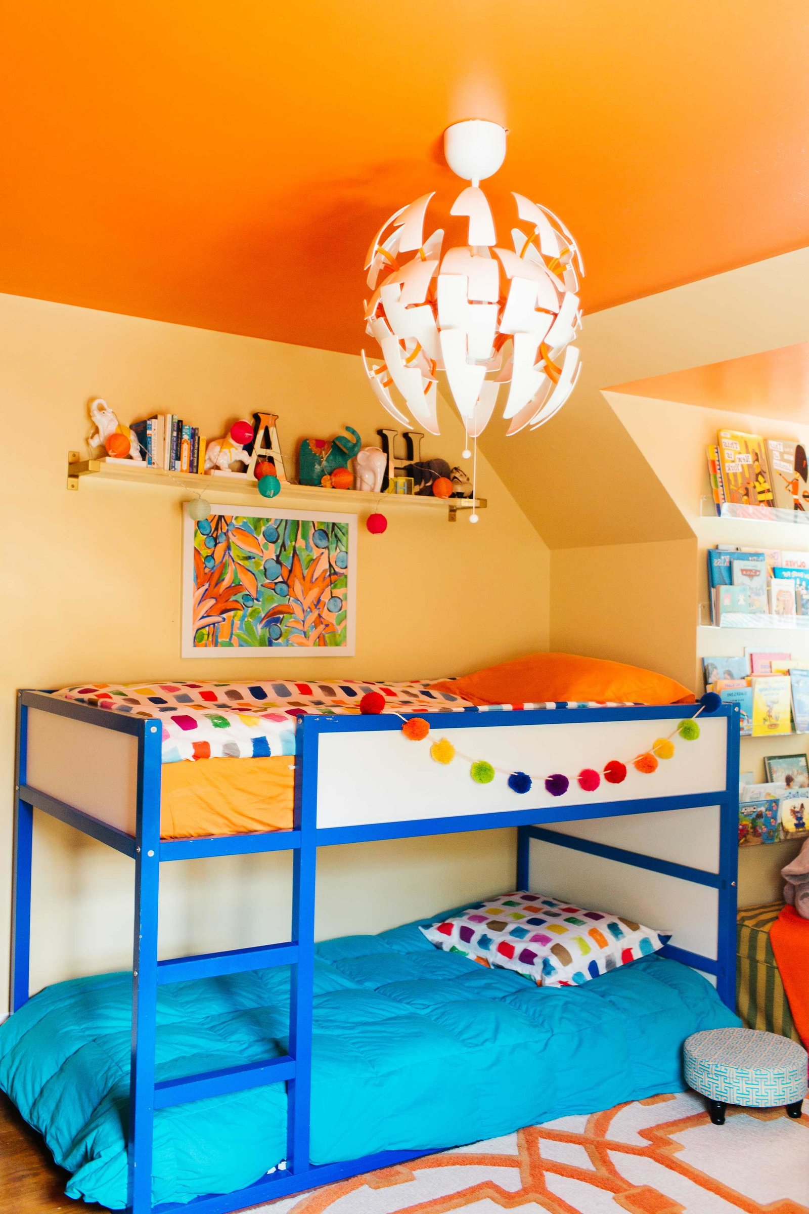 A boys bedroom with blue bunk beds and pom pom garland.