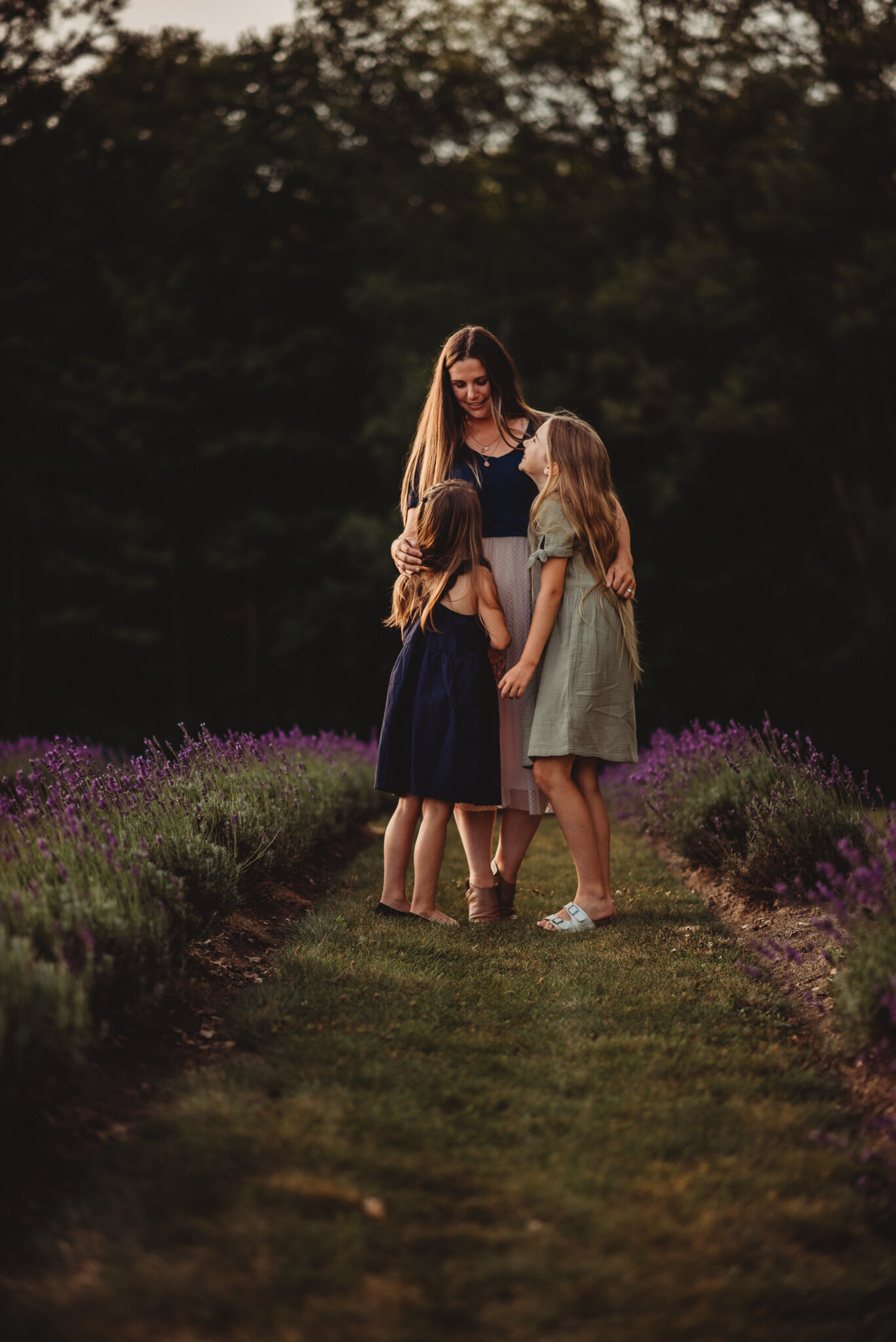 Mother hugging her two daughters in a lavender field