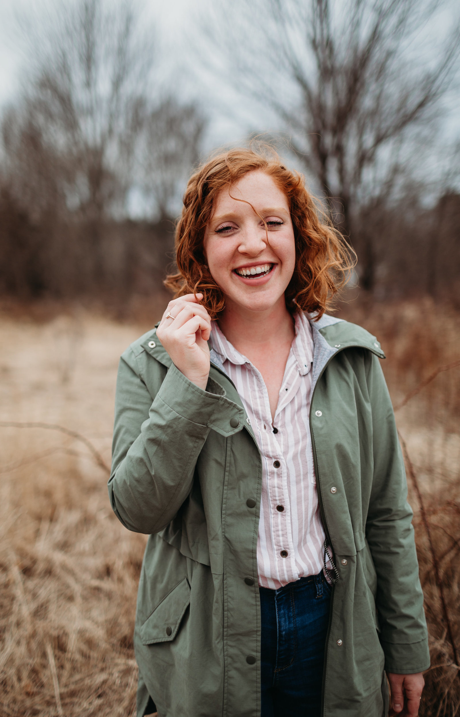redheaded woman grabs hair and laughs at camera during headshot session