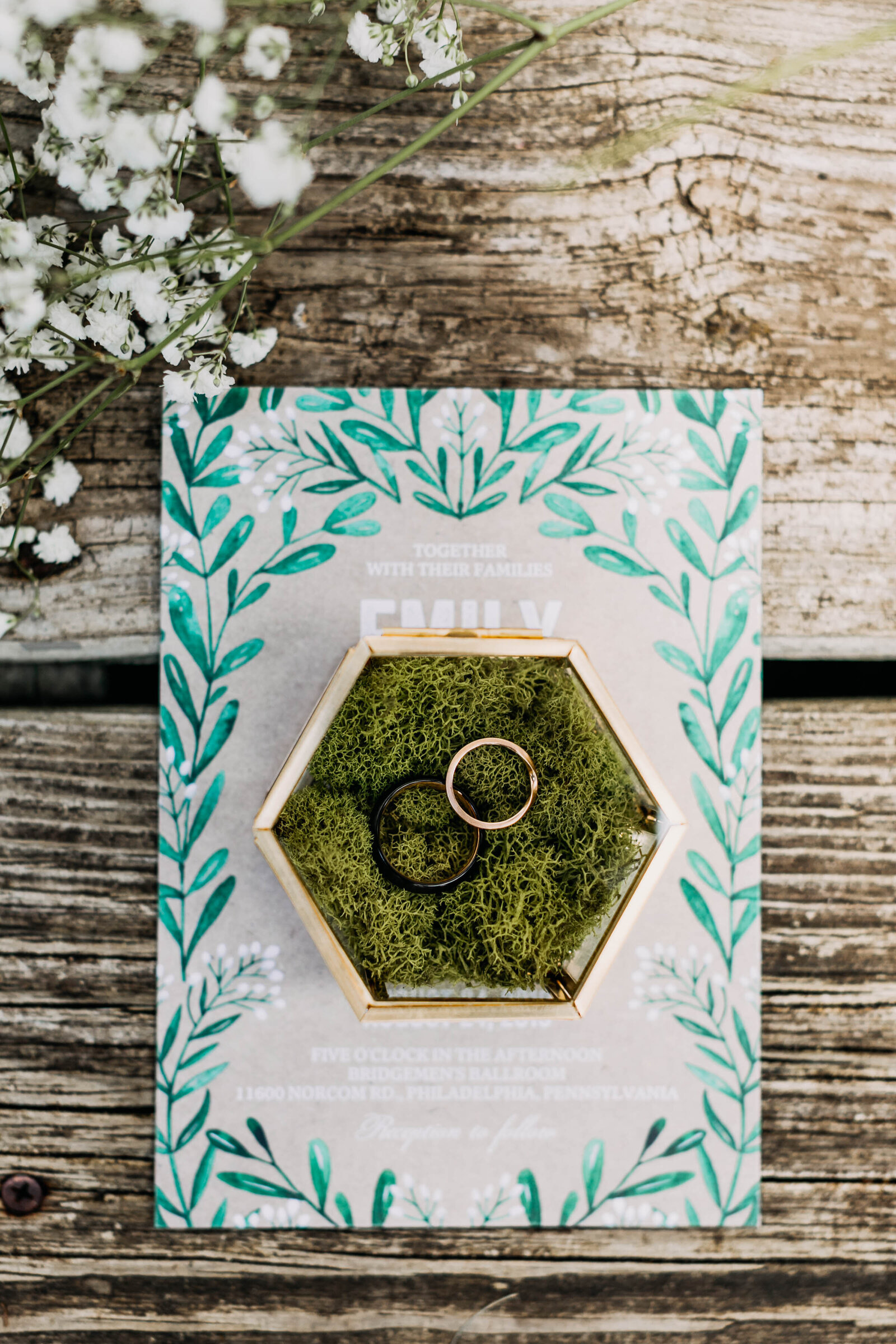 wedding rings in jewelry box with moss