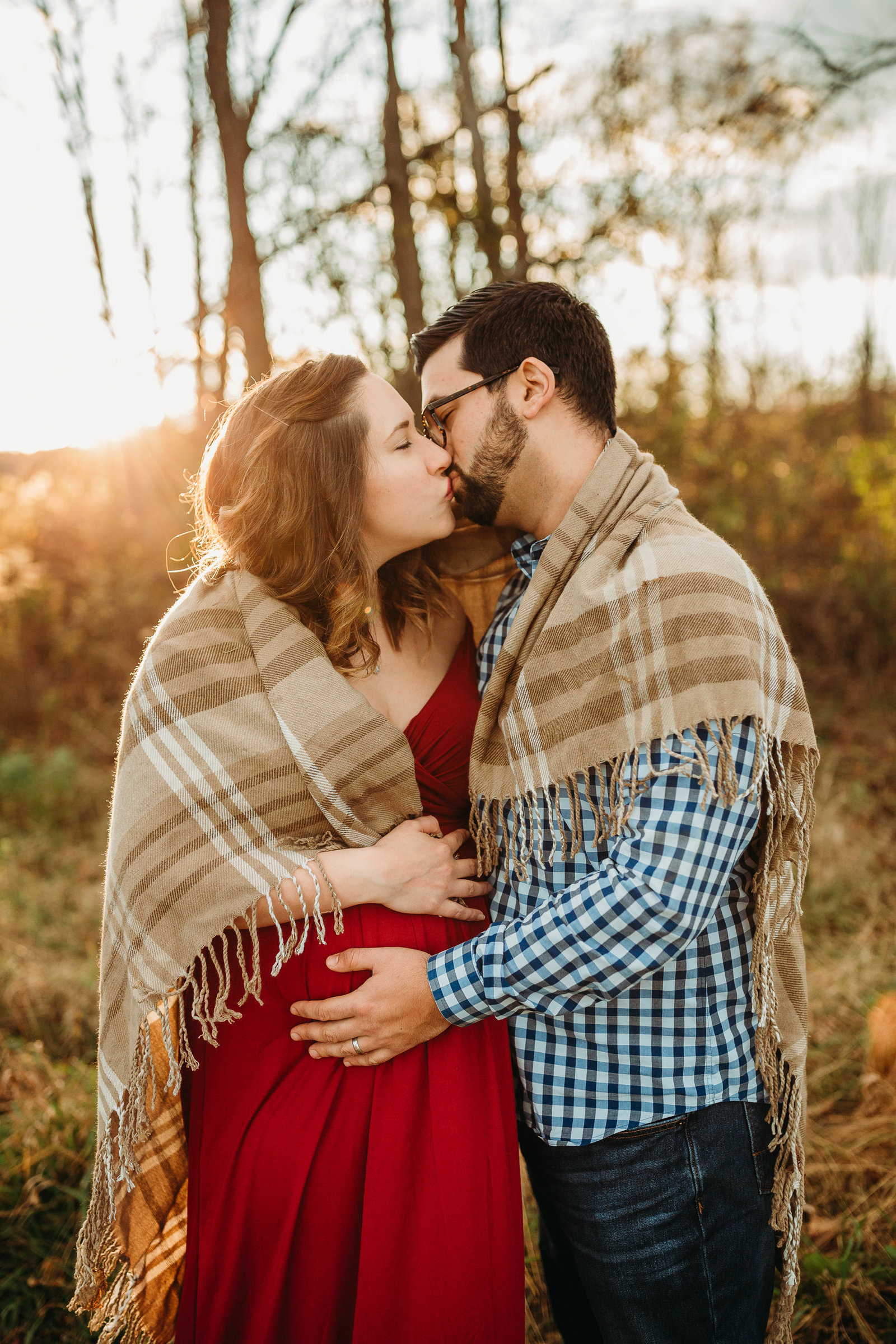 pregnant couple kisses while wrapped in plaid blanket in maternity photos in framingham ma