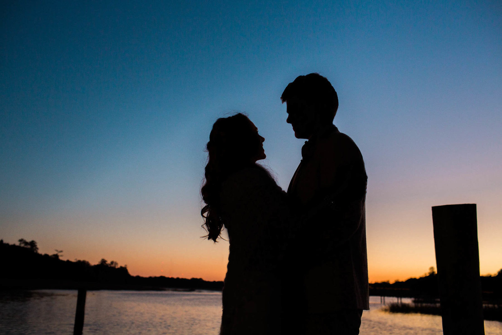 Bride and groom stand on dock at sunset, Boone Hall Plantation, Charleston, South Carolina