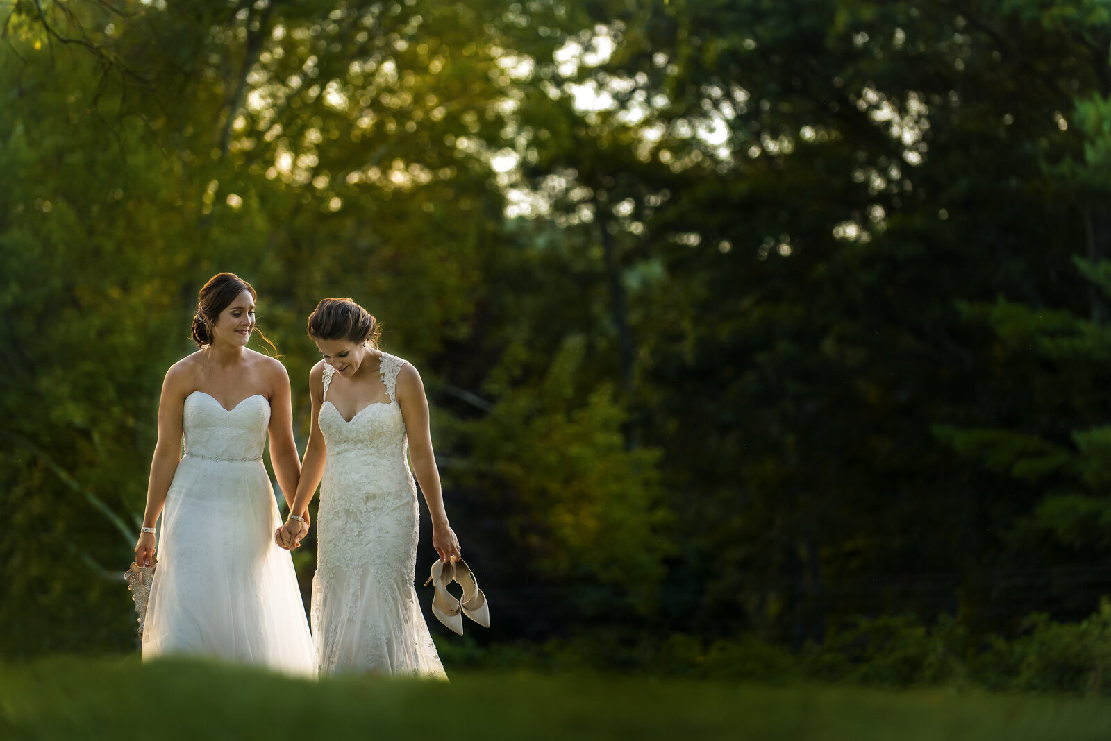 Brides walking together hand in hand in a lush green field at waterloo village in nj