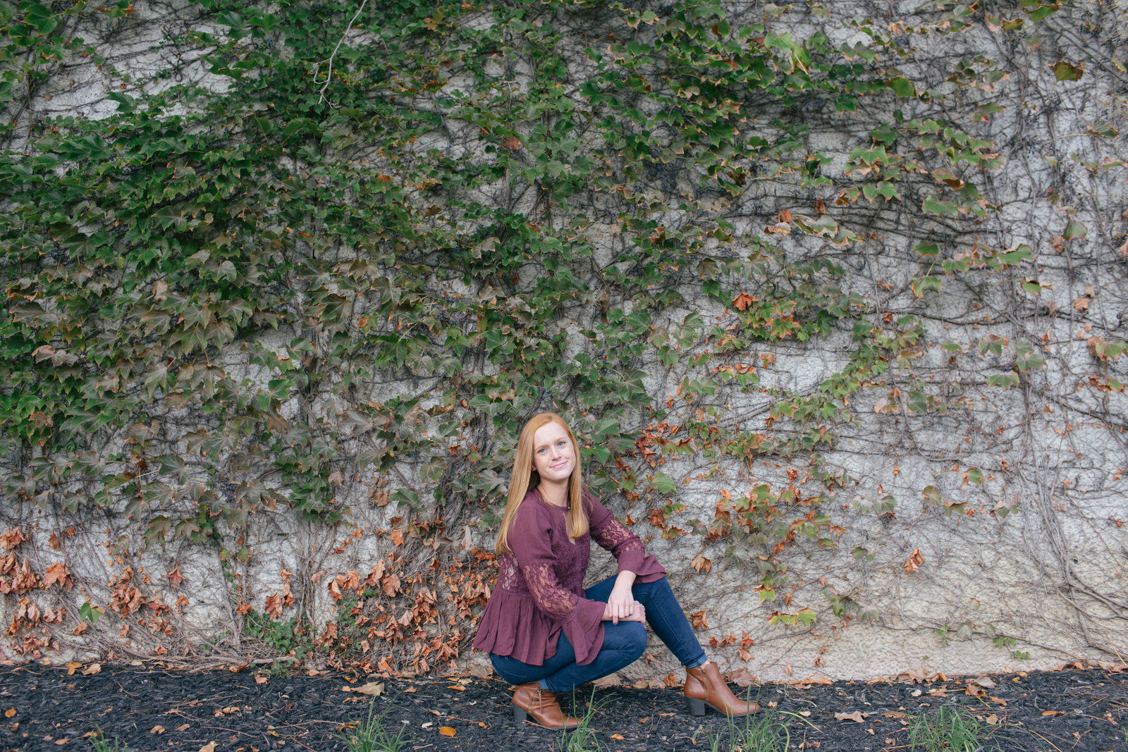 senior girl kneels in front of ivy covered stone wall in station square in downtown pittsburgh
