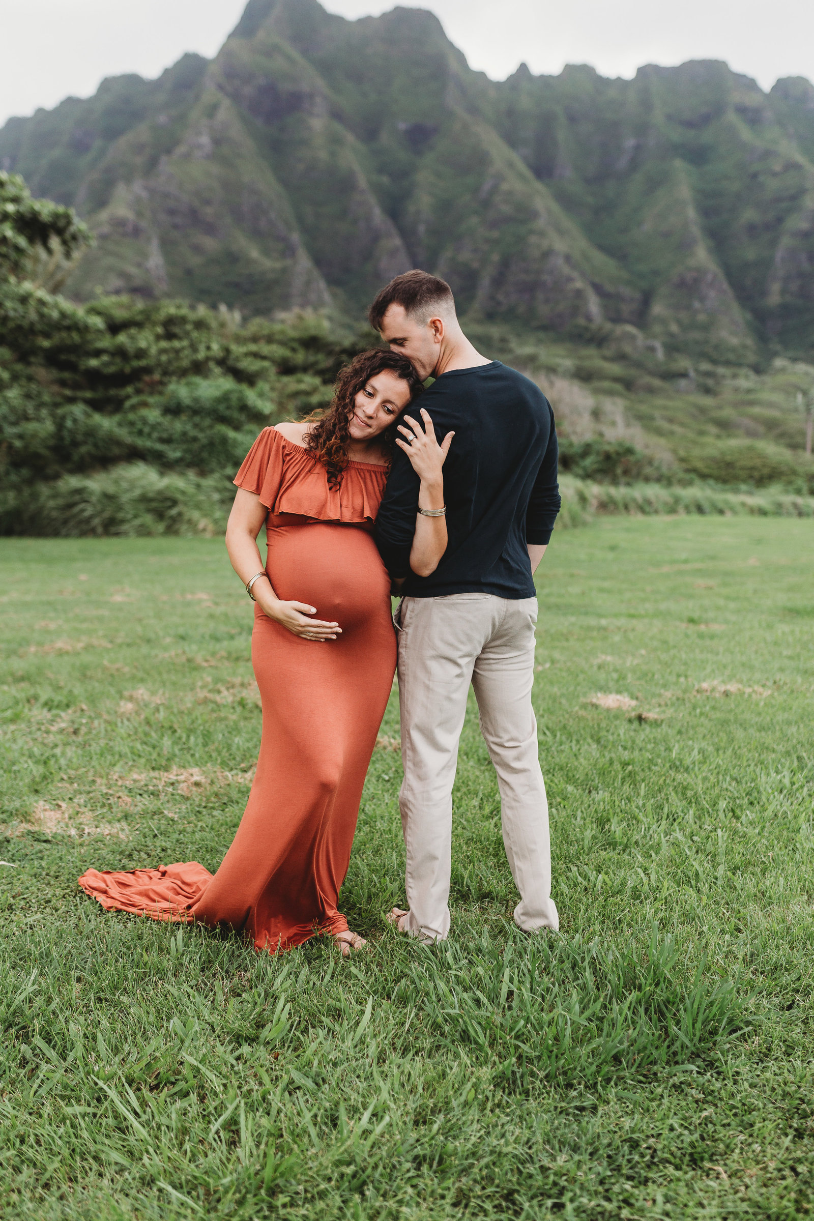 Couples Maternity Photography Shoot - Pregnant Couple standing in the grass with the woman cradling her belly - Honolulu, Oahu, Hawaii - Brooke Flanagan Maternity Photographer
