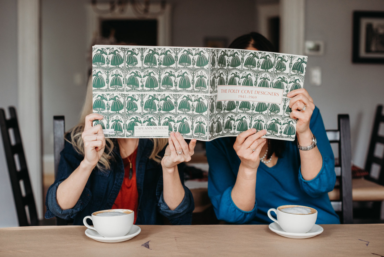 two women hide behind design magazine while drinking coffee