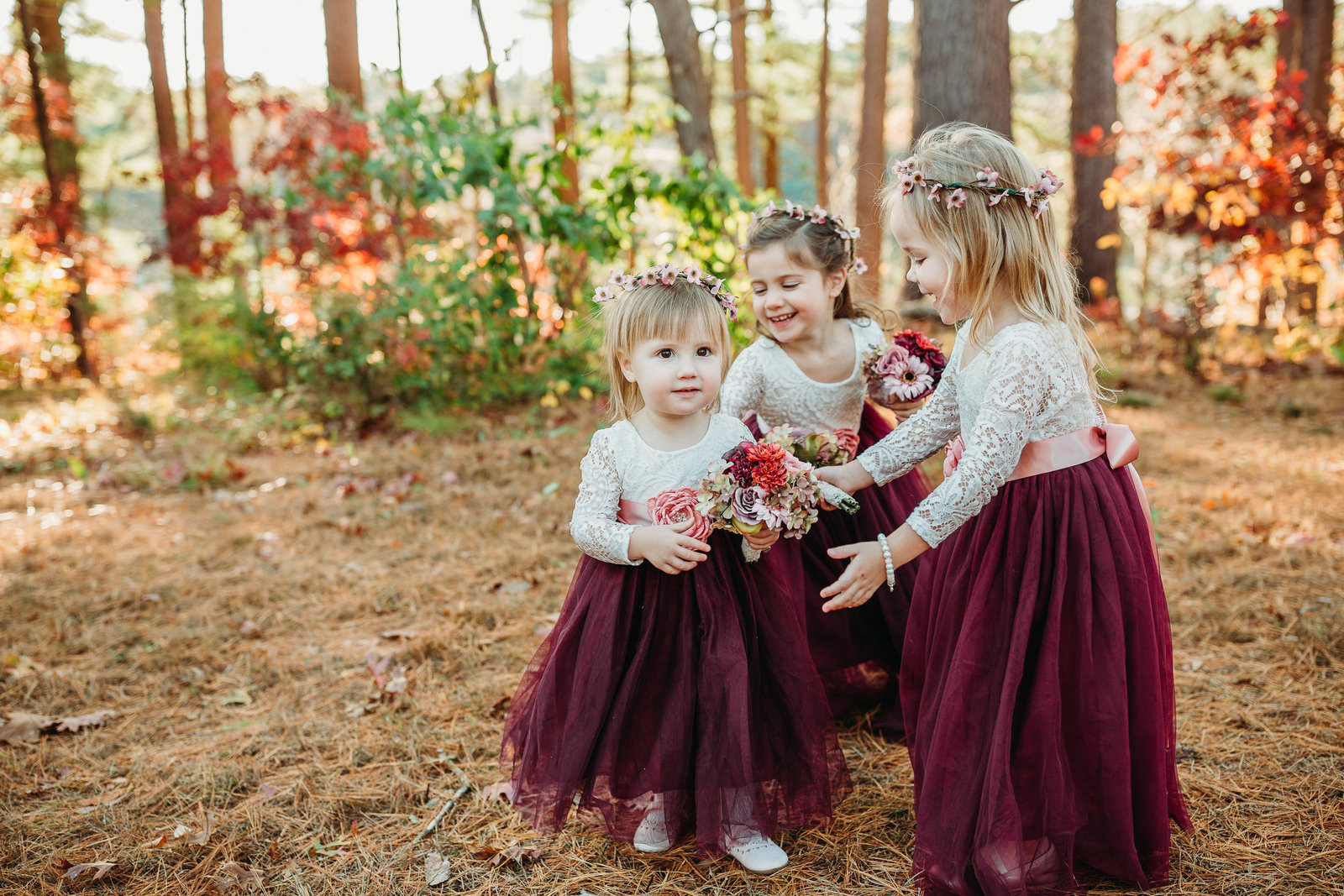 flower girls chase one another during burgundy autumn wedding in mass