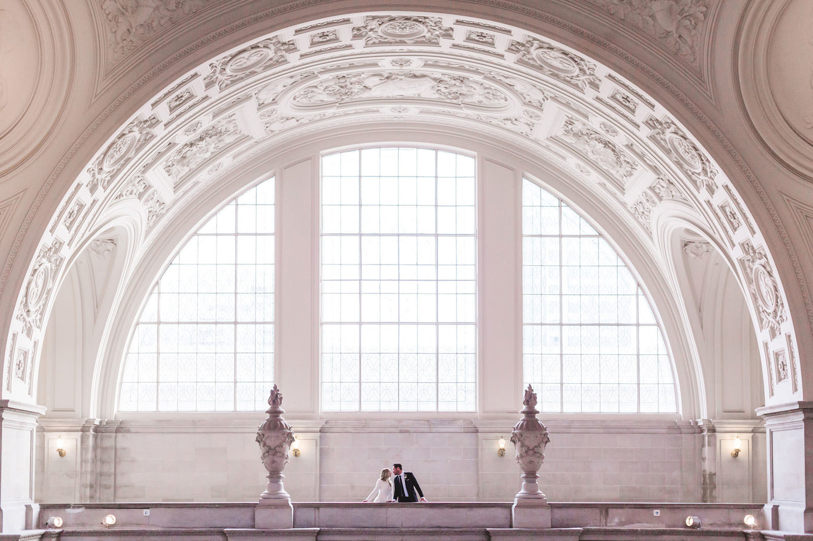 4th floor couple from afar framed by epic arch