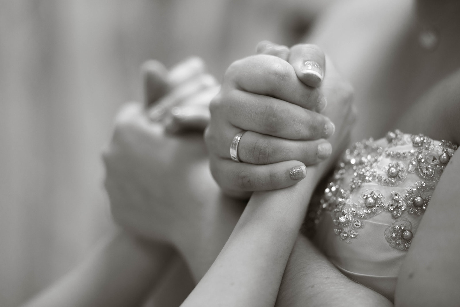 bride holds her maid of honor's hands as her dress is hooked